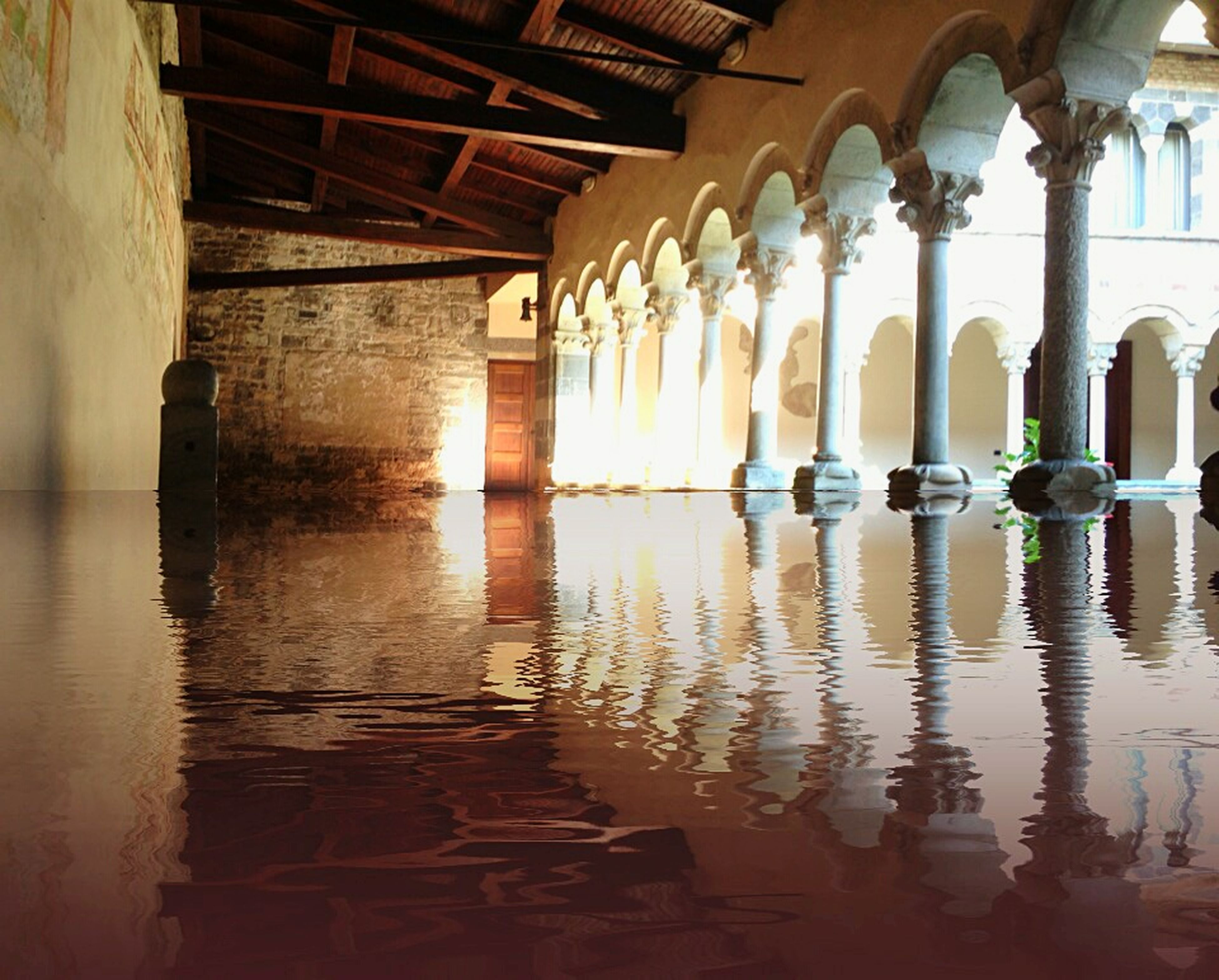 indoors, architecture, built structure, architectural column, arch, in a row, column, reflection, ceiling, water, corridor, interior, below, support, flooring, empty, diminishing perspective, no people, day, colonnade