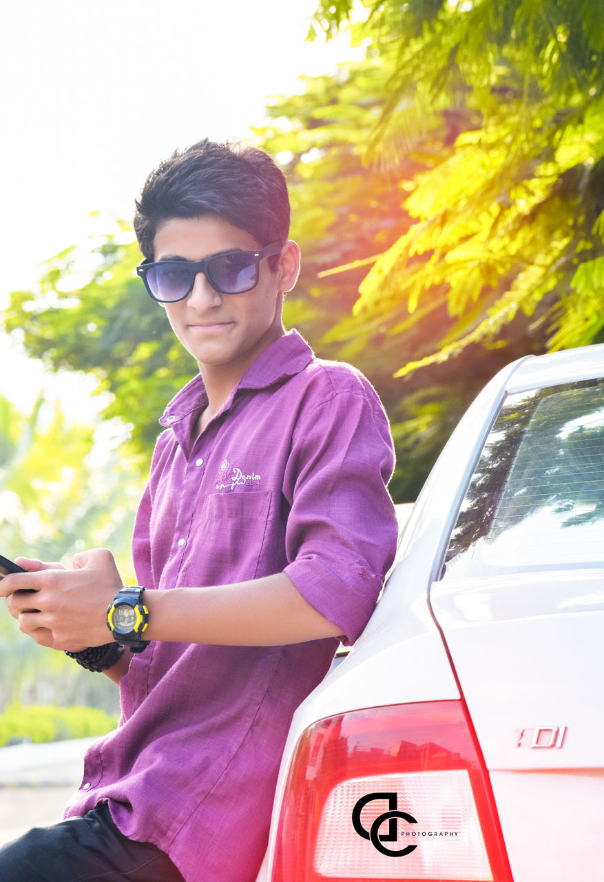 sunglasses, car, transportation, real people, young adult, one person, land vehicle, outdoors, mode of transport, casual clothing, lifestyles, communication, day, young men, leisure activity, tree, young women, looking at camera, technology, wireless technology