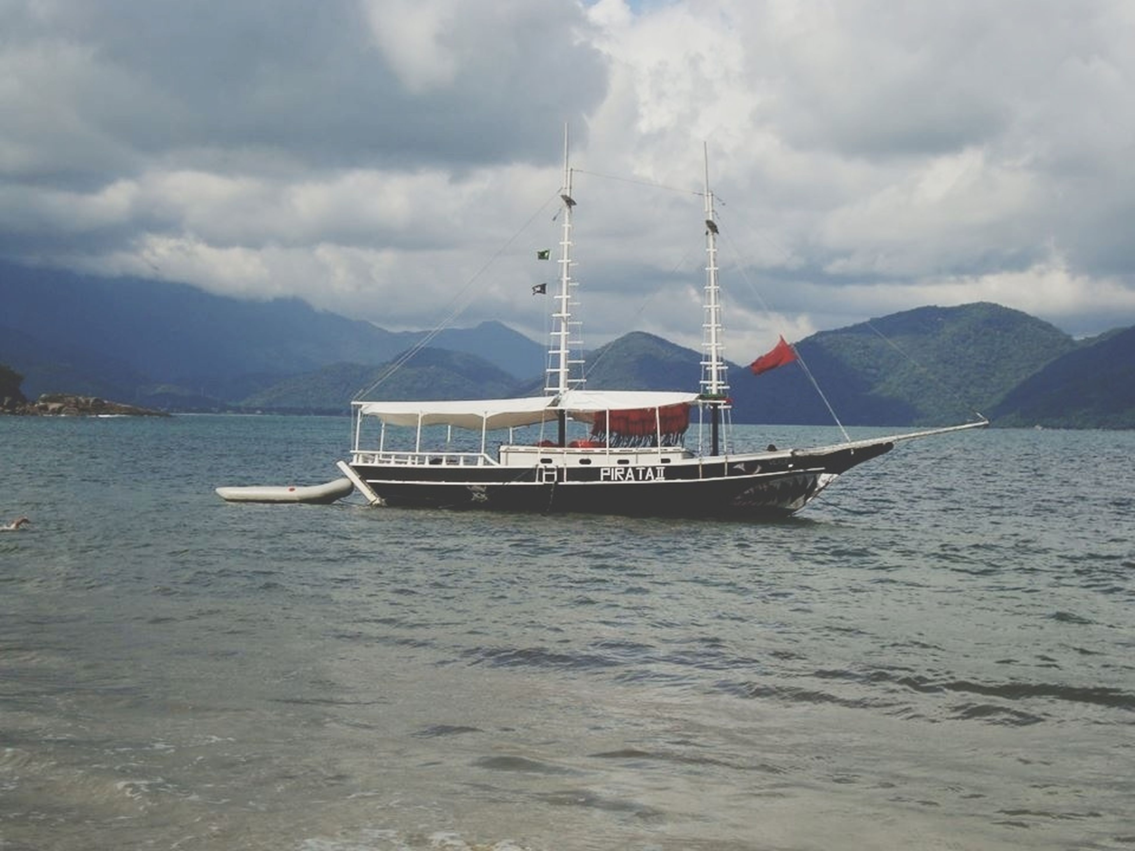 nautical vessel, transportation, boat, mode of transport, water, sky, mountain, sea, cloud - sky, waterfront, moored, cloudy, sailing, tranquil scene, tranquility, travel, scenics, nature, sailboat, cloud