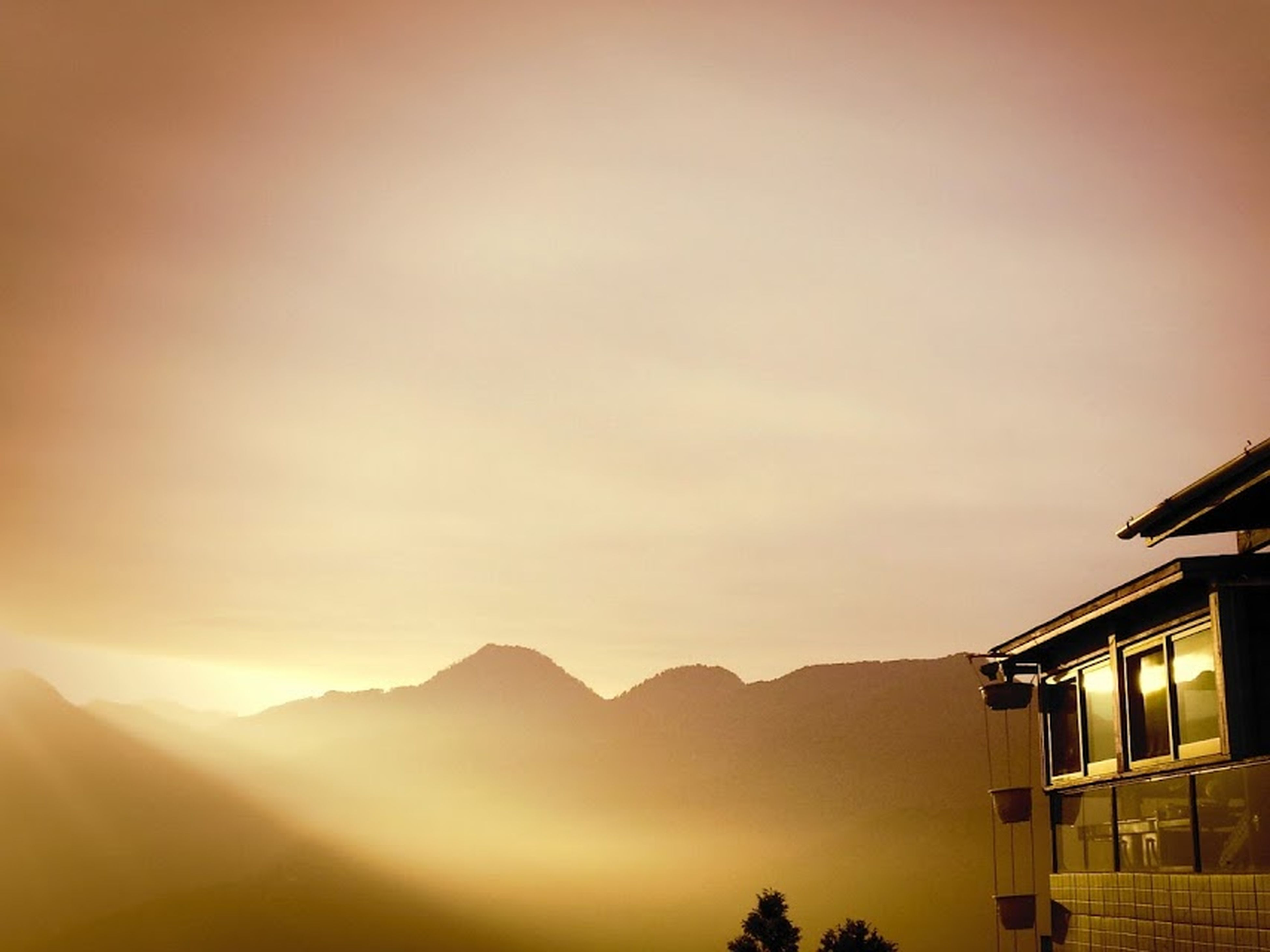 sunset, building exterior, mountain, architecture, built structure, house, sky, scenics, beauty in nature, silhouette, nature, tranquility, tranquil scene, mountain range, orange color, residential structure, low angle view, sunlight, copy space, outdoors