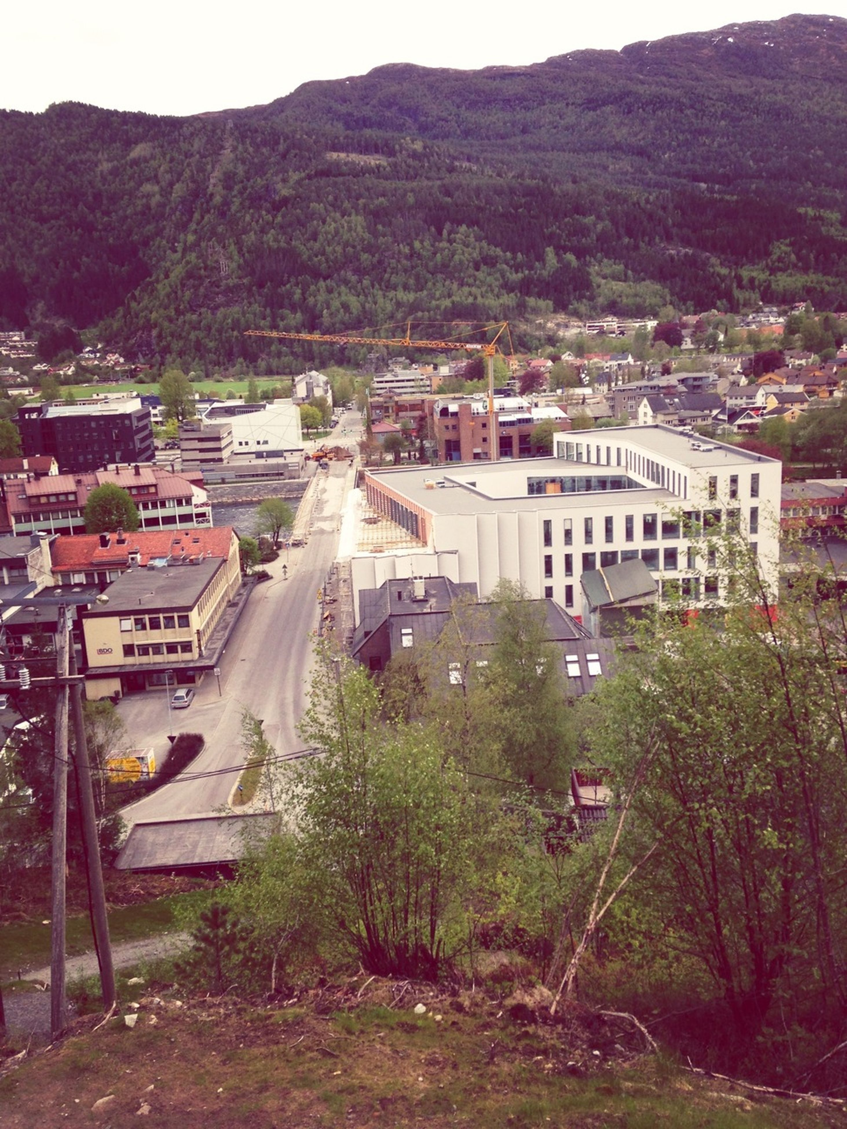building exterior, mountain, architecture, built structure, tree, house, residential building, residential structure, high angle view, town, mountain range, residential district, road, street, townscape, city, outdoors, sky, landscape, village