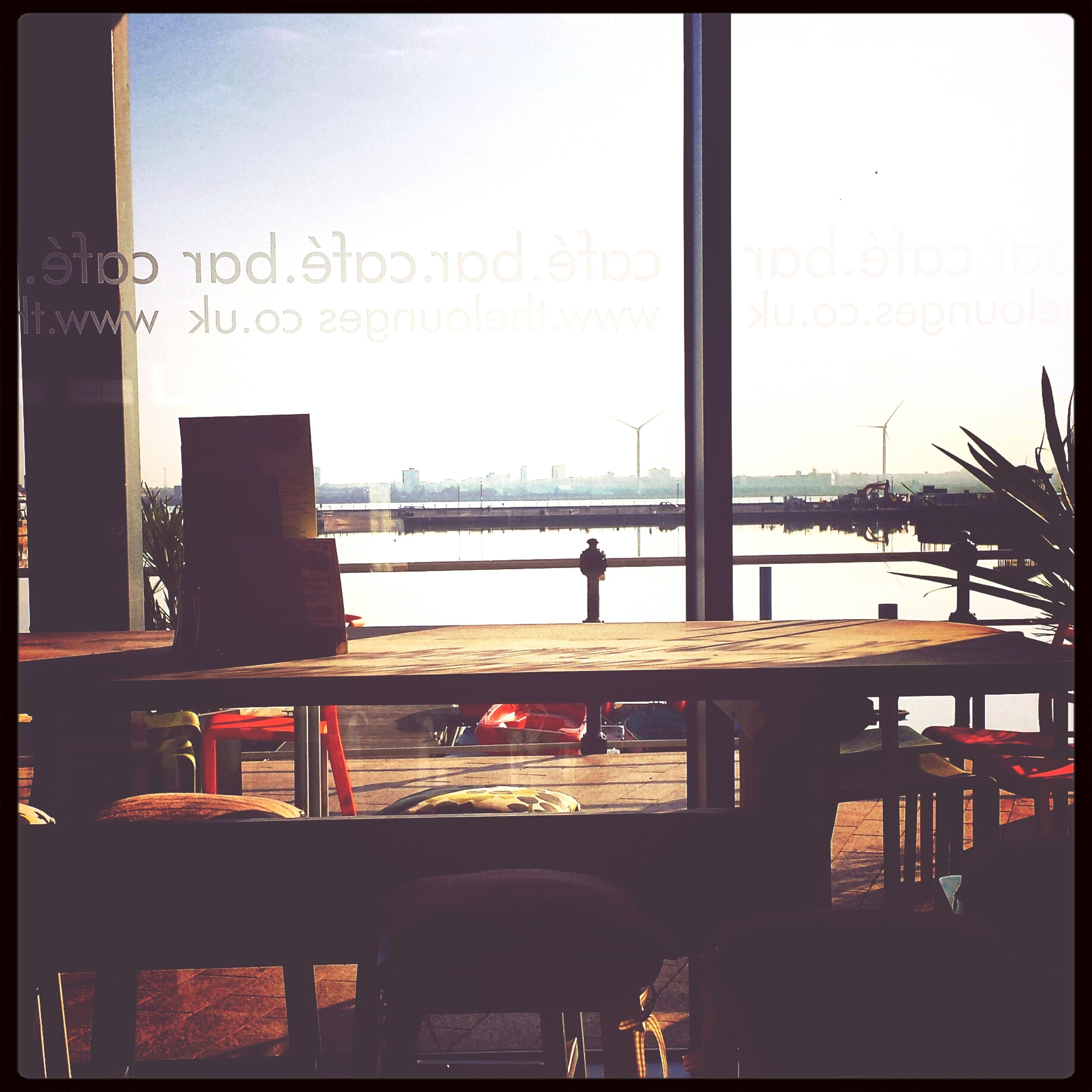 transfer print, auto post production filter, indoors, built structure, chair, architecture, clear sky, men, restaurant, silhouette, window, table, text, copy space, sky, communication, glass - material, sitting, railing