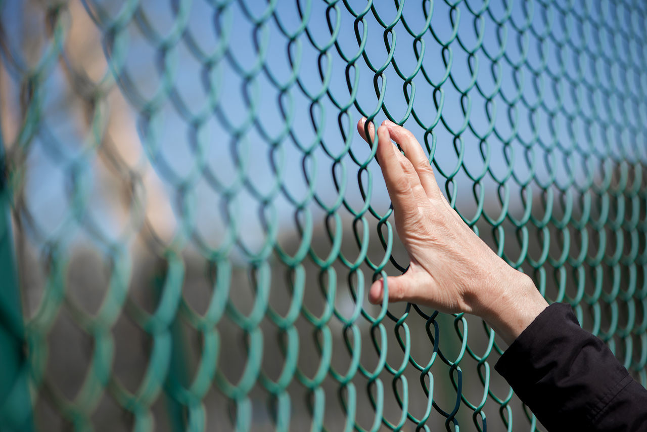 Abstract Adult Adults Only Backgrounds Baseball - Sport Baseball Helmet Baseball Player Broken Dreams Chainlink Fence Close-up Day Fingers Human Body Part Human Body Parts Human Hand Leisure Activity One Person Outdoors People Playing Field Real People Refugees Sport Team Sport Woman