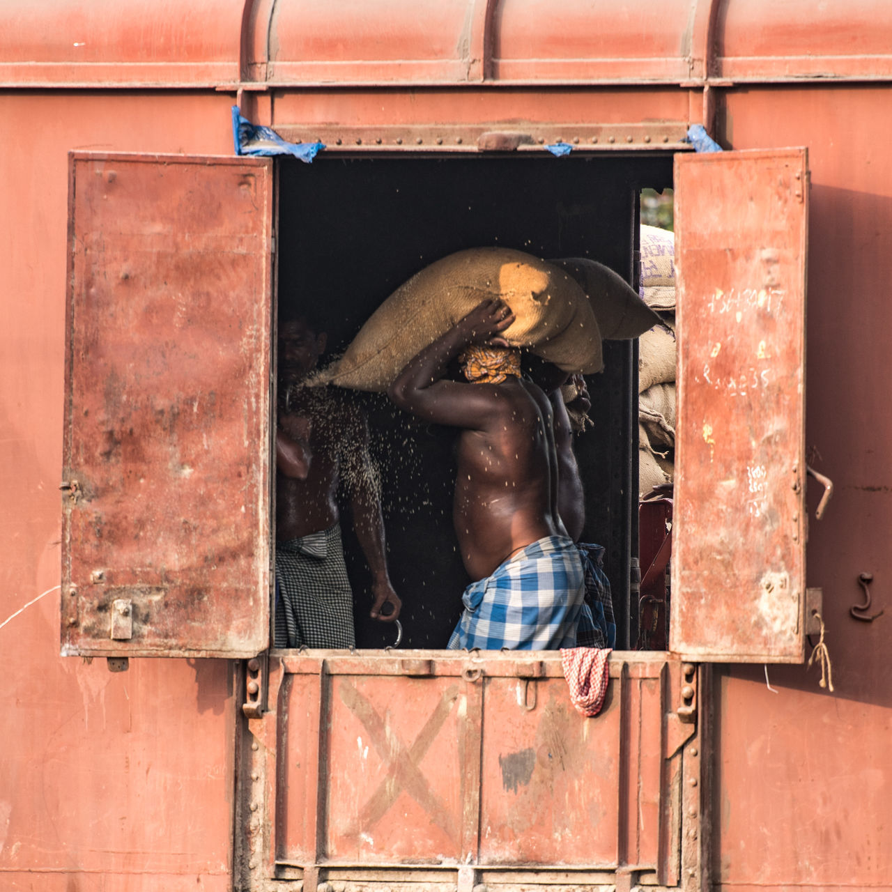Unloading the train is hard manual labour. ASIA Day Goods India Indian Indian Railways Labour Men Outdoors People Rail Transportation Rice Southern Railways Sweat Trade Train Transportation Travel Unloading Work Working Working Hard