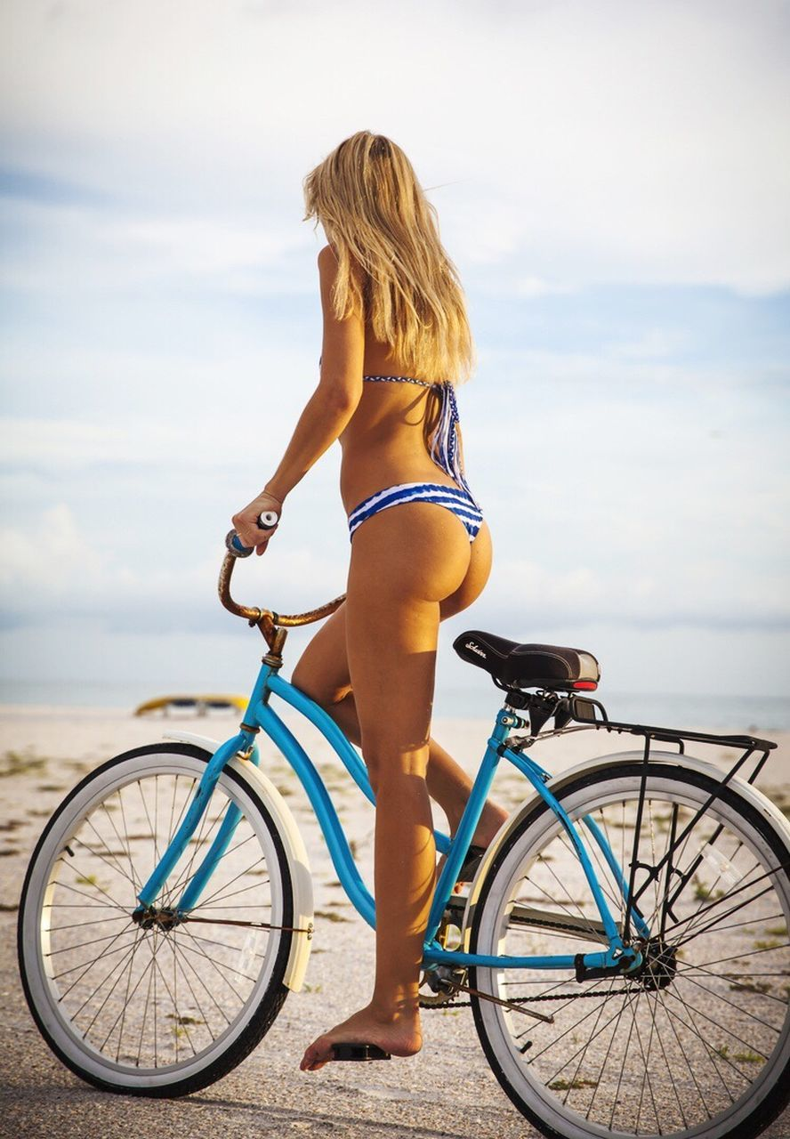 leisure activity, one person, real people, sea, transportation, full length, mode of transport, young adult, bicycle, lifestyles, young women, sky, outdoors, water, nature, day, rear view, standing, beach, horizon over water, beauty in nature, blond hair, people
