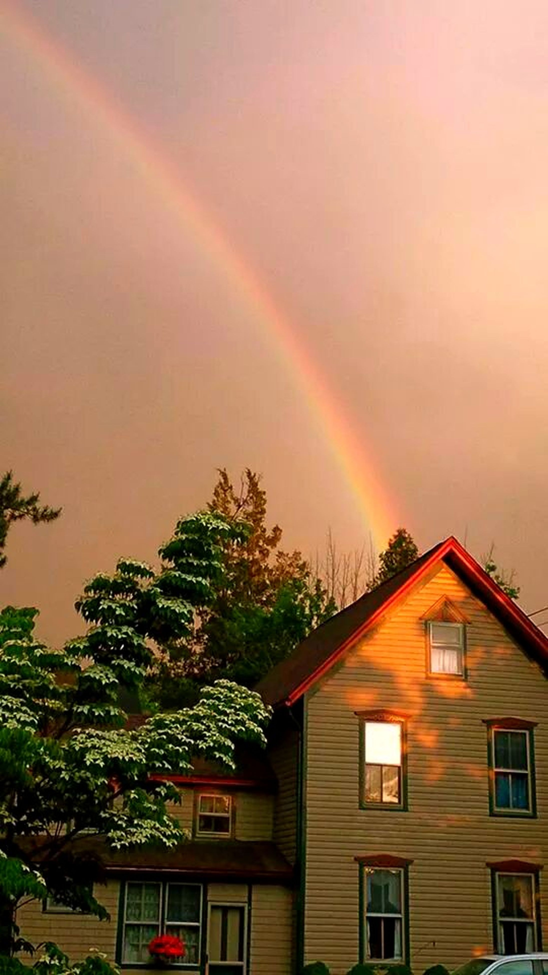 building exterior, architecture, built structure, house, tree, residential structure, sky, residential building, rainbow, low angle view, sunset, high section, nature, roof, growth, beauty in nature, cloud - sky, outdoors, no people, multi colored