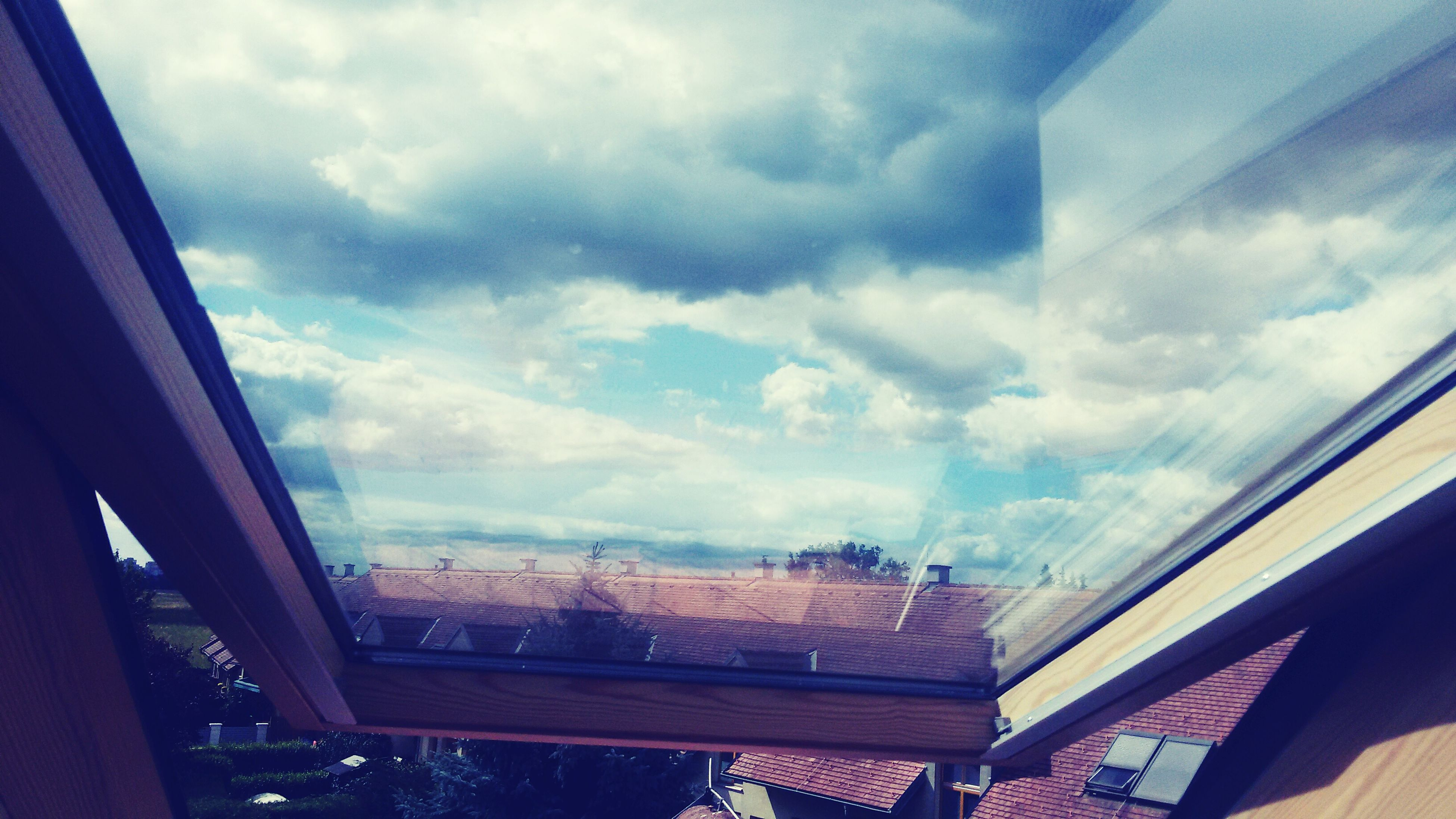 architecture, built structure, window, indoors, sky, cloud - sky, building exterior, low angle view, glass - material, cloudy, transparent, roof, cloud, residential structure, railing, house, day, ceiling, building, balcony