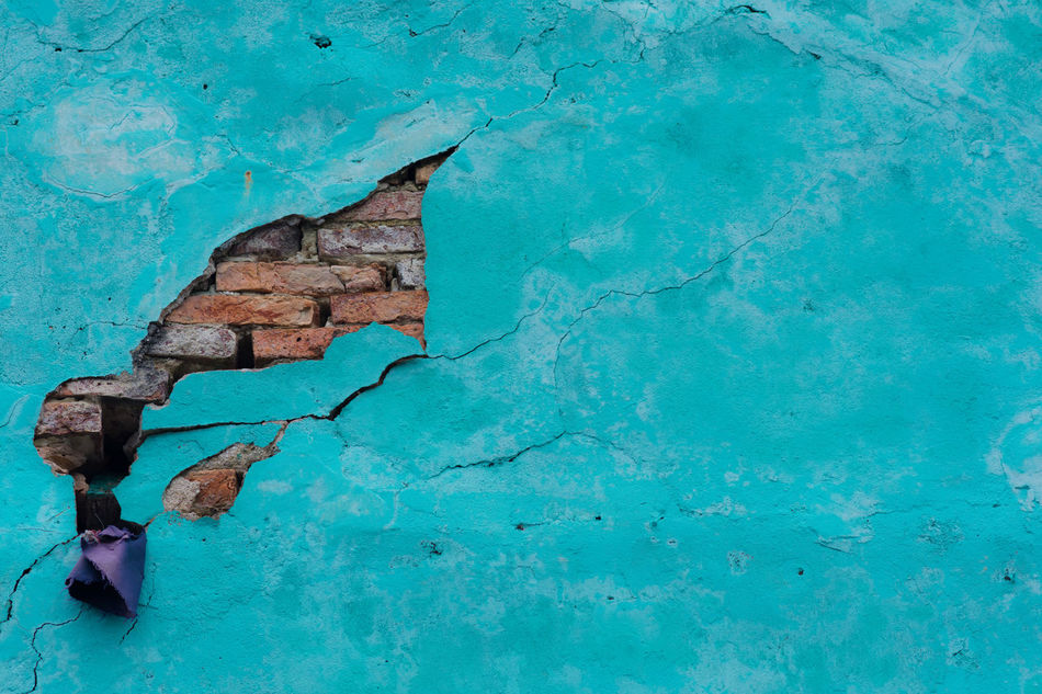 Cracked turquoise plastered wall exposing brick work. Brick Brick Work Building Building Exterior Colour Crack Cracked Damaged Exposed Flat Missing Repair Simple Turquoise Wall Washed