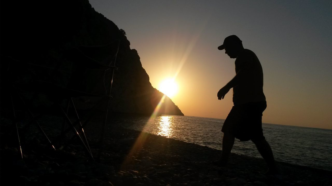 sunset, silhouette, sun, sea, water, nature, beauty in nature, scenics, sunlight, beach, real people, sky, men, outdoors, tranquility, leisure activity, standing, lifestyles, one person, horizon over water, vacations, full length, people