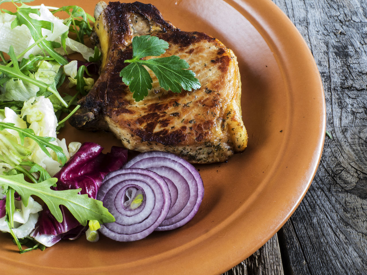 Roasted pork chop on a plate with a green salad, red onion on an old wooden weathered table Chop Close-up Food Food And Drink Freshness Green Healthy Eating High Angle View Indoors  Leaf No People Old Onion Plate Pork Ready-to-eat Relaxing Roasted Salad Table Vegetable Weathered Wooden