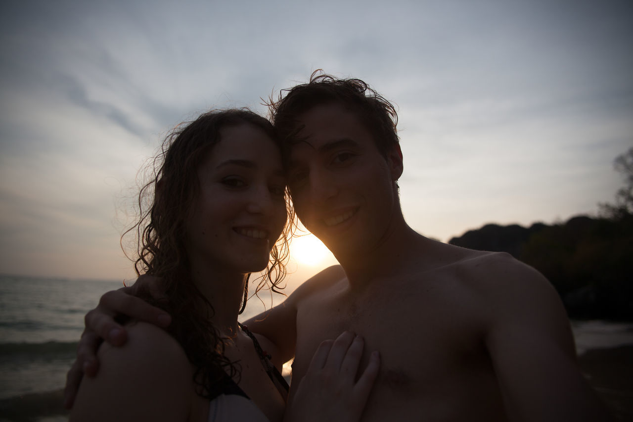 two people, togetherness, sea, real people, leisure activity, young women, sky, love, outdoors, sunset, water, nature, beach, young adult, vacations, shirtless, lifestyles, bonding, couple - relationship, day, looking at camera, friendship, standing, smiling, happiness, beauty in nature, men, beautiful woman, horizon over water, close-up, people