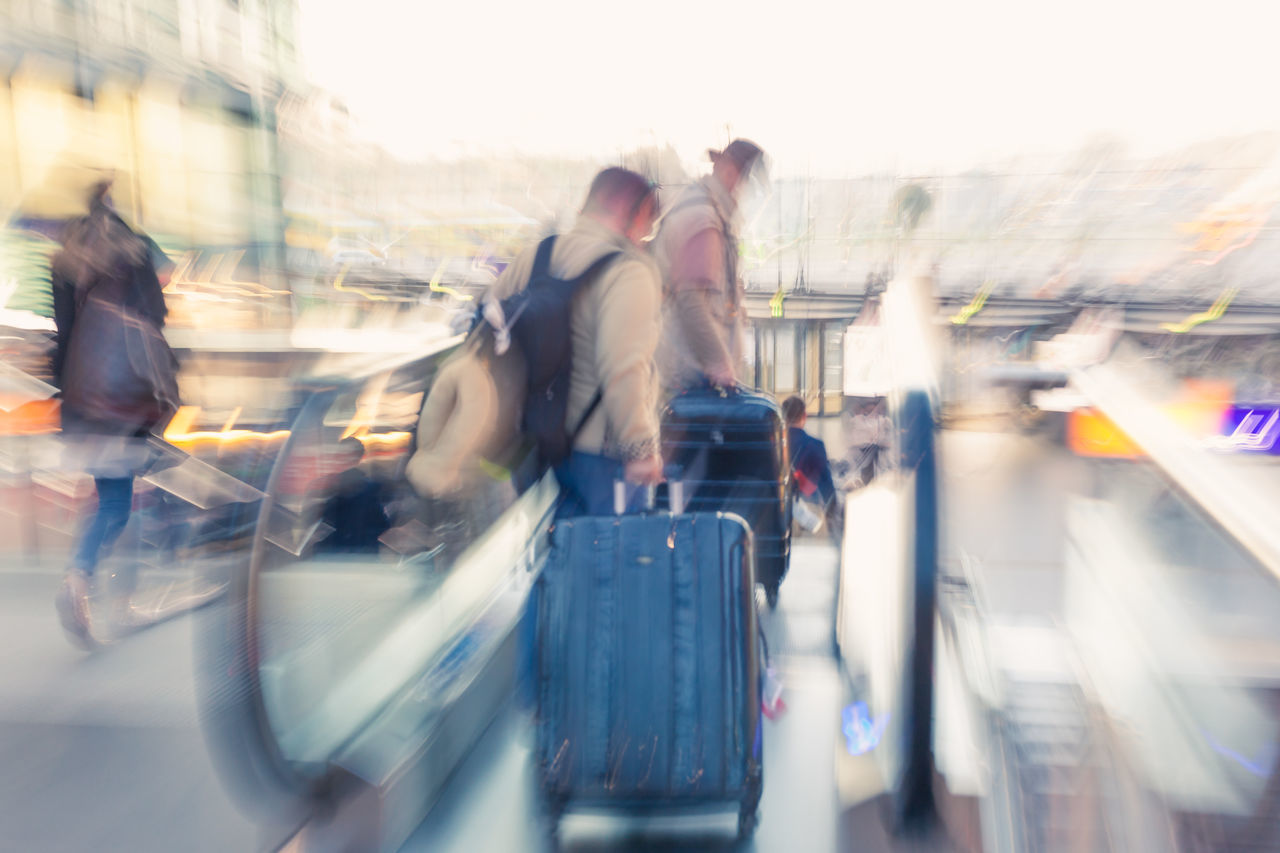 Travelers with luggage on escalator motion blur zoom effect at sunset Casual Clothing City City Life Commuter Escalator Escalators Leisure Activity Luggage Men Motion Motion Blur Moving People Real People Travel Traveling Two People