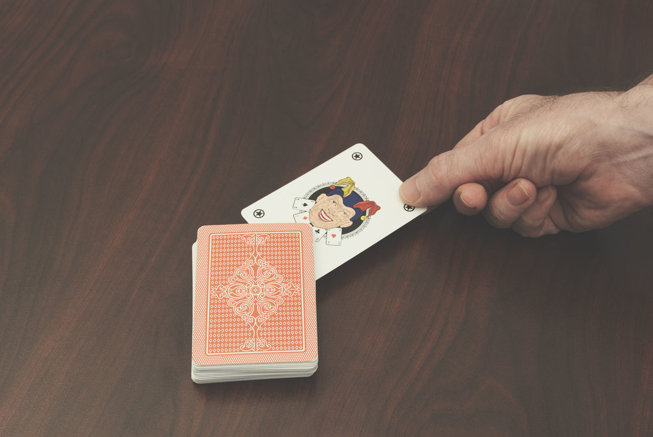 hand picking up a joker card Card Cards Chance Choice Close-up Concept Gambling Game Holding Human Hand Indoors  Joker Jolly Leisure Games Luck One Person Picking Playing Poker Poker - Card Game Real People Table Unexpected