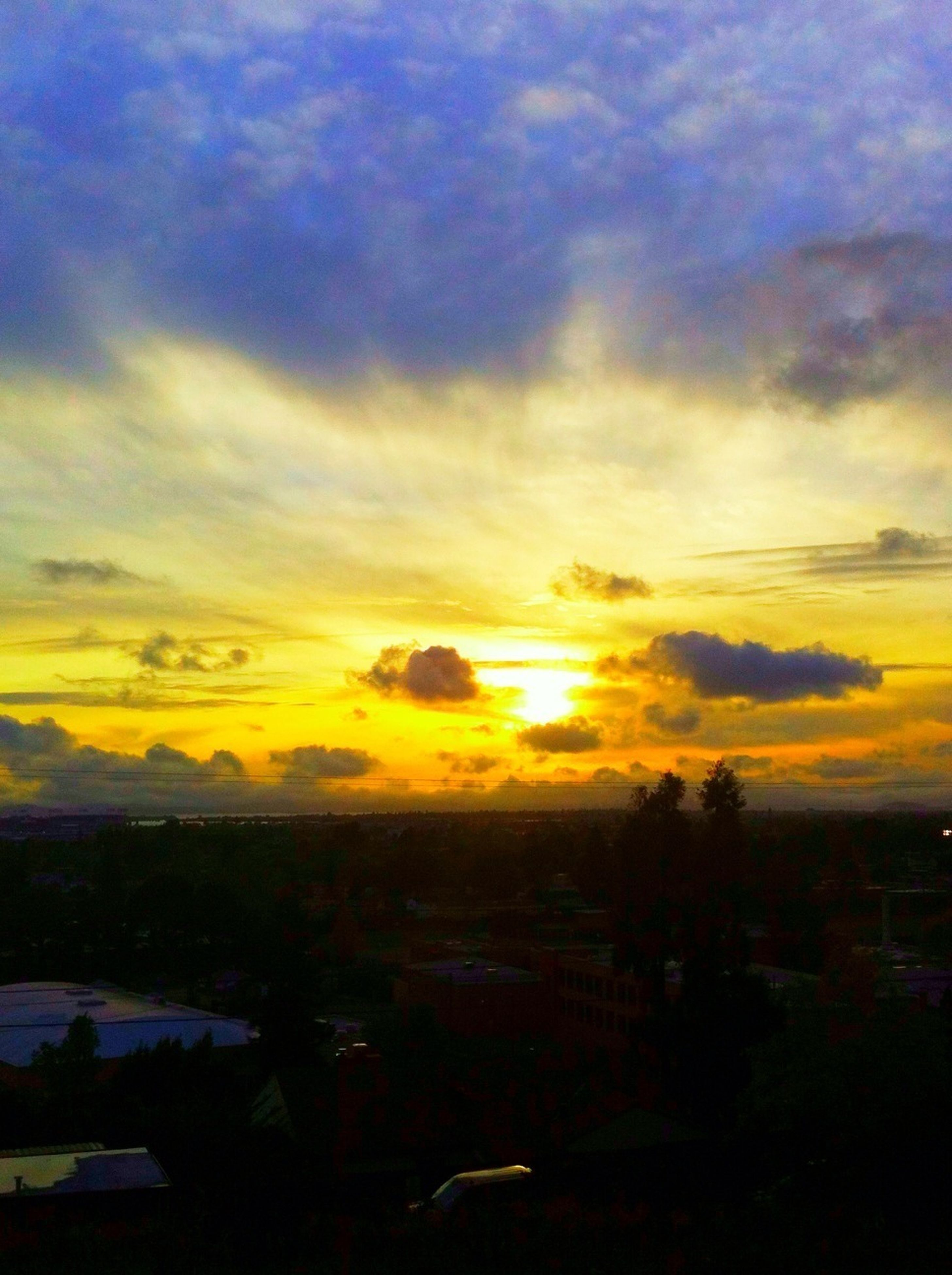 sunset, sky, orange color, scenics, cloud - sky, beauty in nature, landscape, tranquil scene, tranquility, cityscape, nature, dramatic sky, idyllic, city, cloud, cloudy, high angle view, building exterior, silhouette, sun
