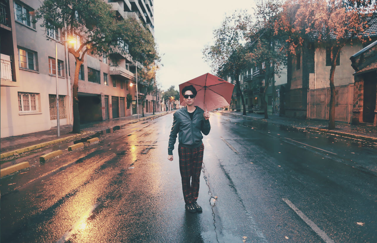 Full length portrait of young man with umbrella standing on city street