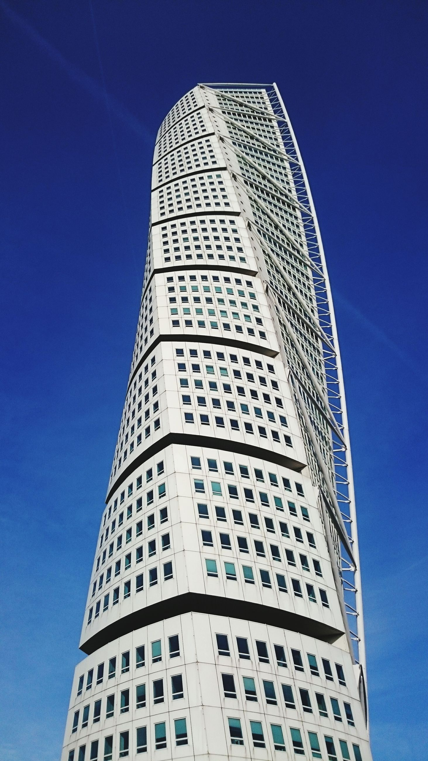 architecture, low angle view, building exterior, built structure, modern, tall - high, blue, skyscraper, city, office building, tower, clear sky, building, glass - material, sky, reflection, day, tall, outdoors, no people