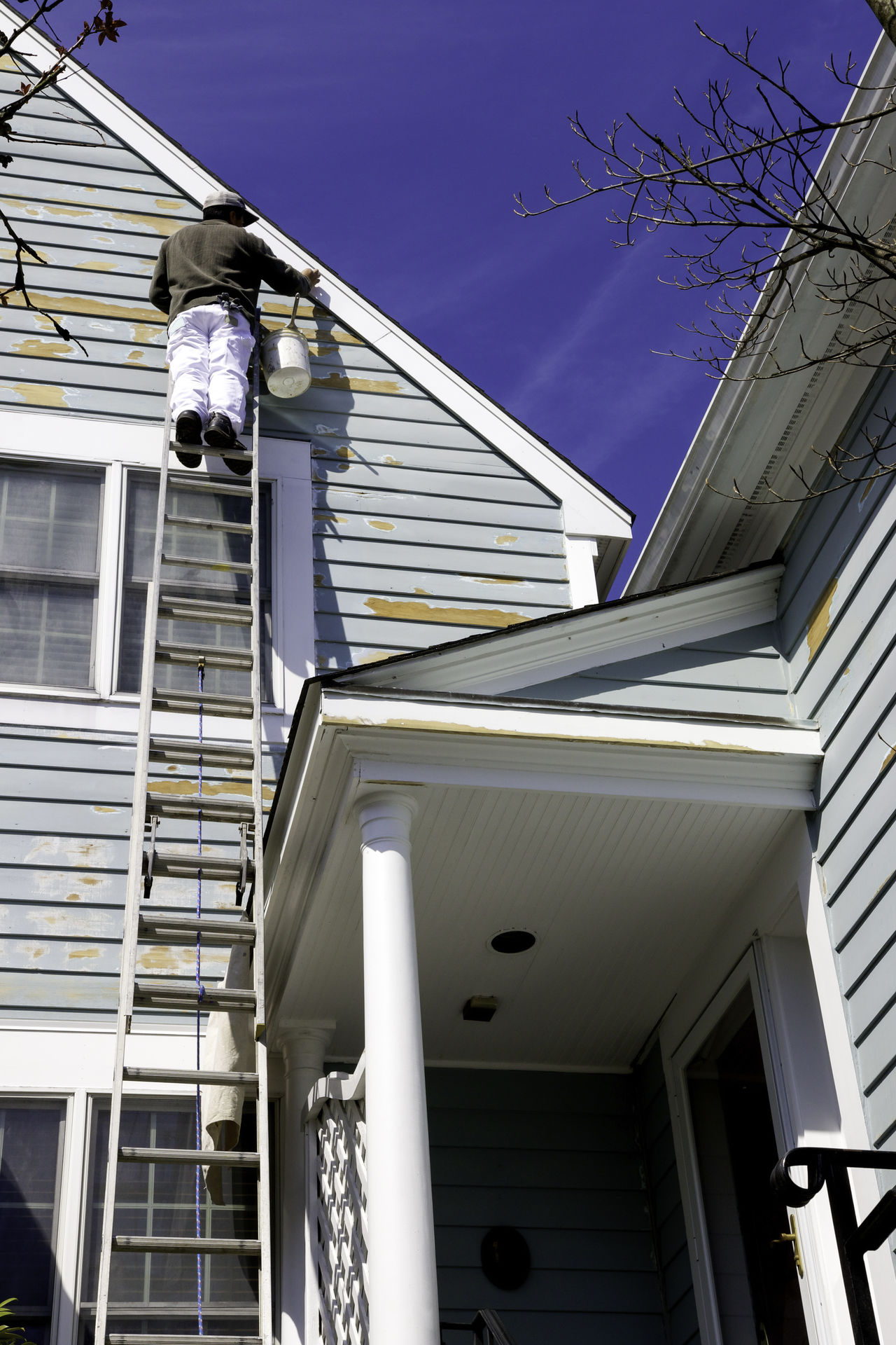 Painting contractor on ladder works on siding of a nice home or condo in white plains, ny on a beautiful day. Blue Sky Condo Contractor Hanging Out Home Home Exterior Homeimprovement House Ladder Pain Painter Siding Trim Trim Work Wood