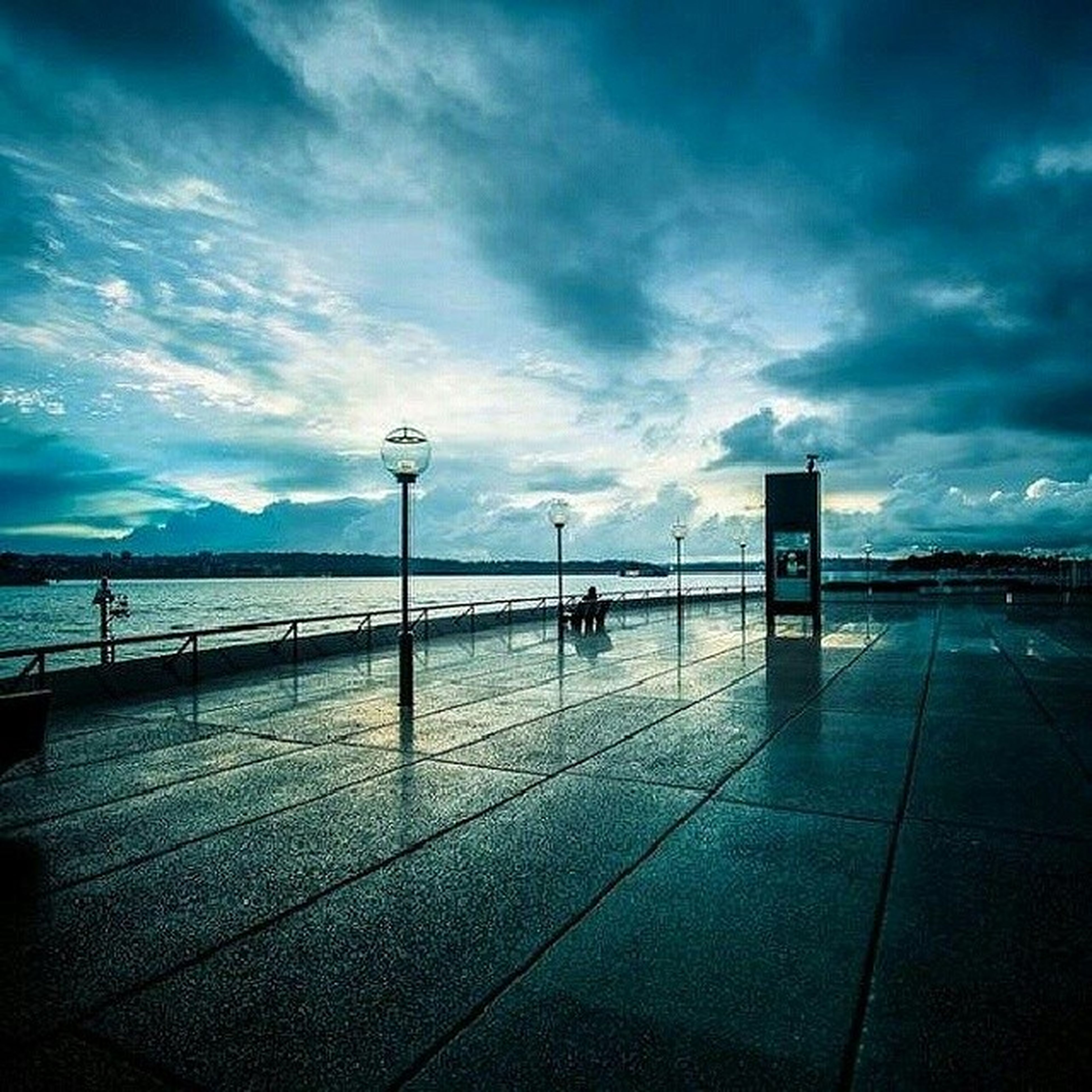 sky, cloud - sky, sea, water, built structure, cloudy, cloud, architecture, street light, blue, beach, nature, railing, horizon over water, connection, outdoors, day, incidental people, tranquility, scenics
