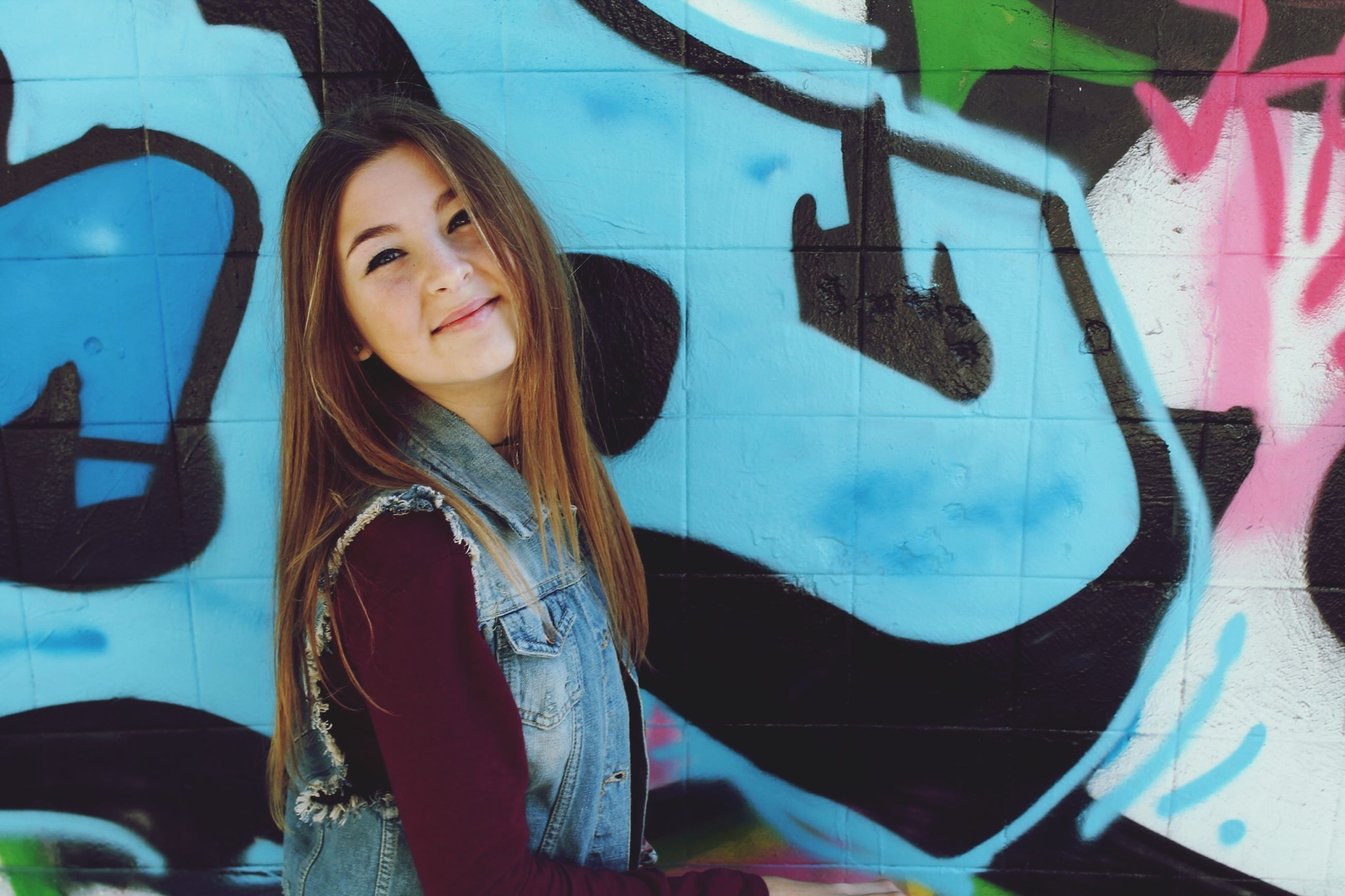young adult, young women, lifestyles, looking at camera, person, portrait, long hair, front view, casual clothing, standing, graffiti, leisure activity, smiling, waist up, three quarter length, wall - building feature, happiness