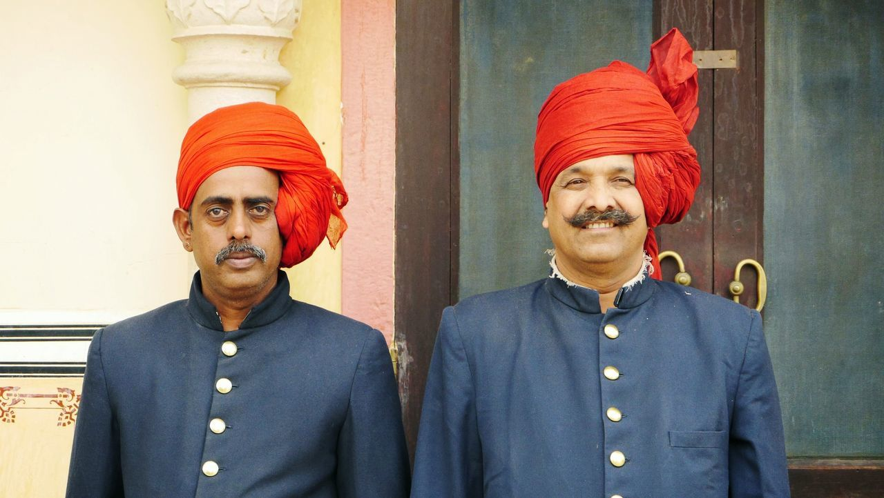 looking at camera, portrait, mature adult, mature men, waist up, real people, two people, standing, turban, day, smiling, outdoors, close-up, young adult, people