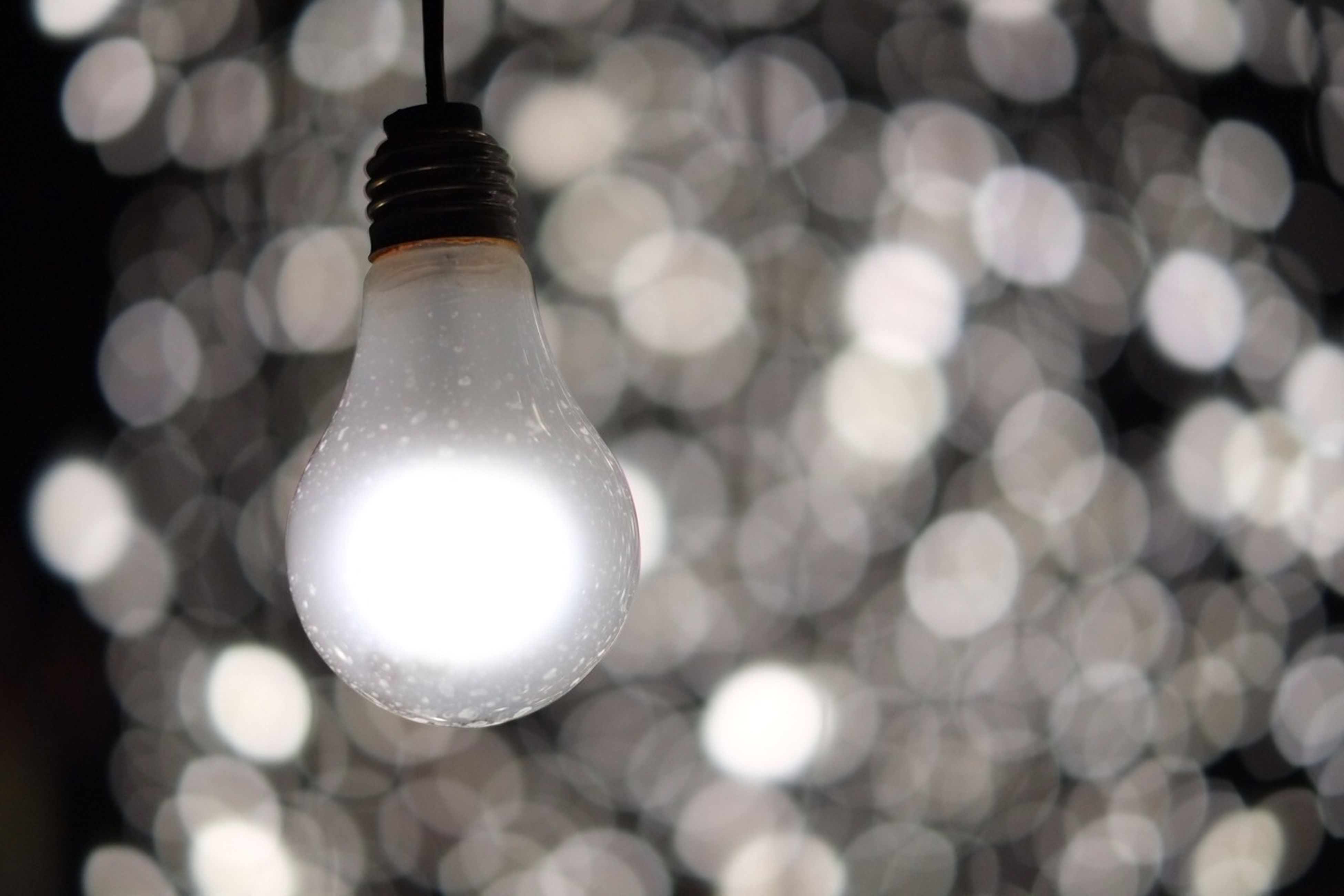 illuminated, lighting equipment, indoors, close-up, light bulb, electricity, focus on foreground, glowing, hanging, electric light, decoration, low angle view, lit, light - natural phenomenon, metal, selective focus, still life, no people, shiny, sphere