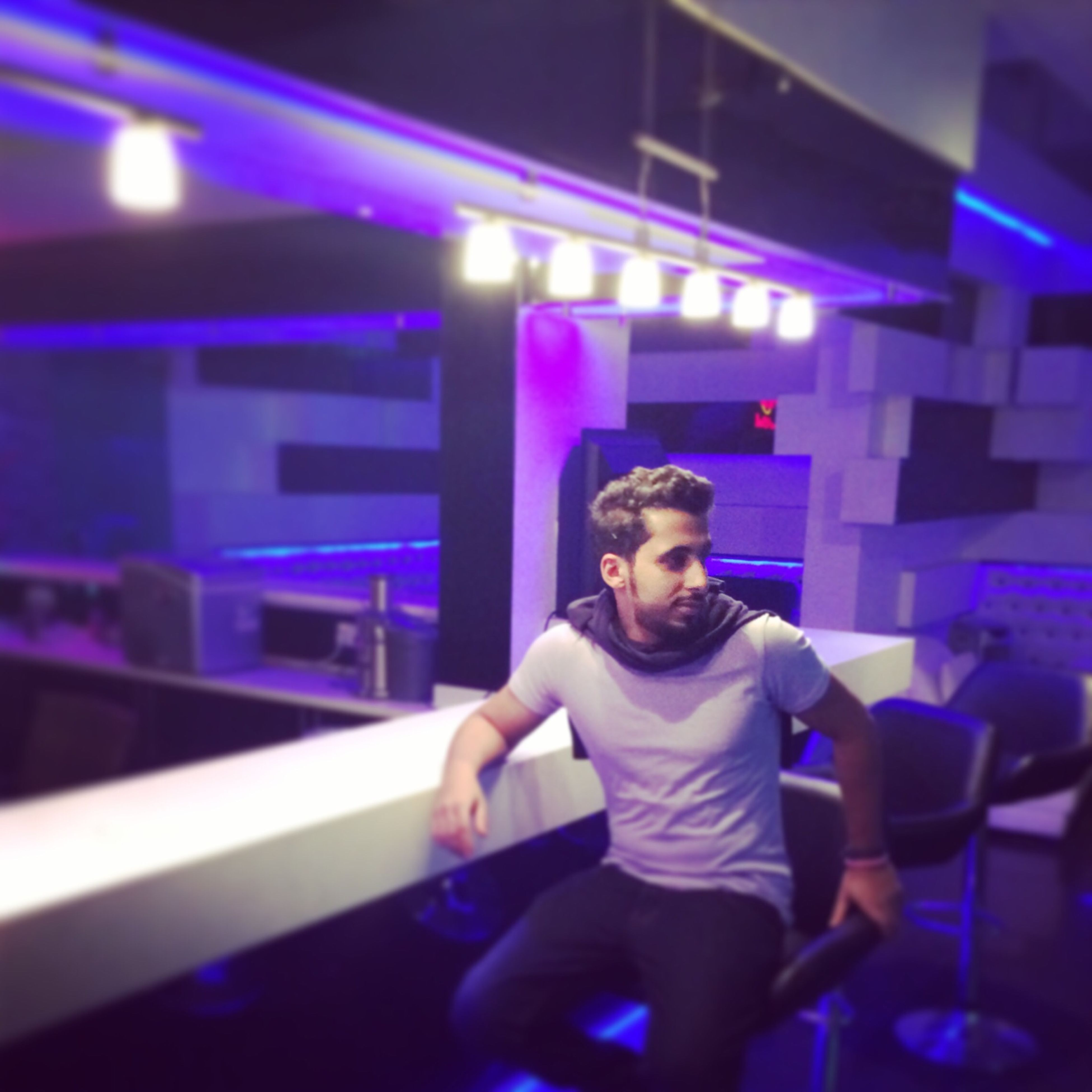 illuminated, indoors, night, lifestyles, leisure activity, lighting equipment, arts culture and entertainment, selective focus, playing, person, music, sitting, casual clothing, focus on foreground, front view, blue, light - natural phenomenon, childhood
