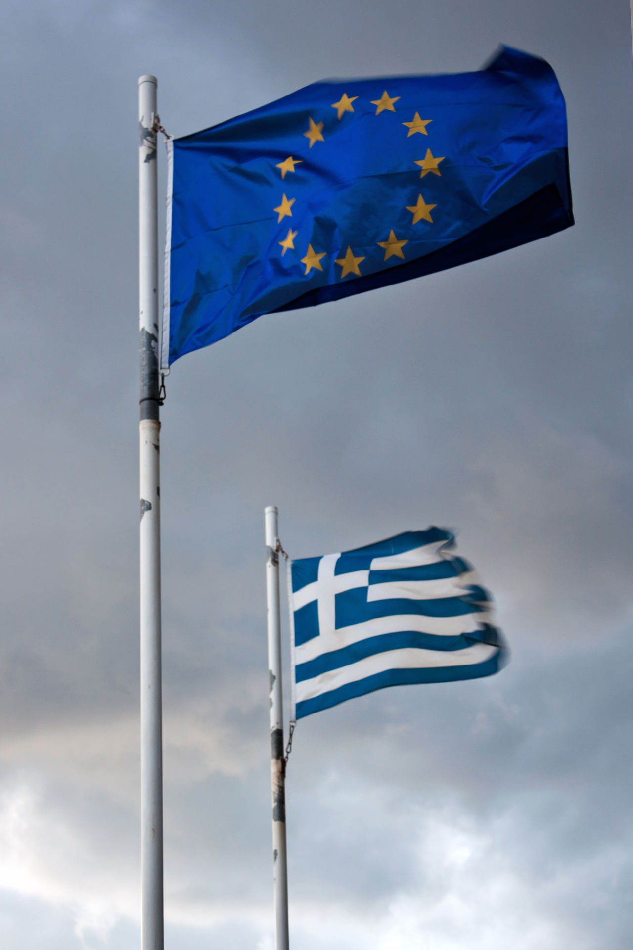 Crisis Day Dynamic Eu Euro Europe European Union Financial Crisis Flag Greece Greece Flag Low Angle View Negotiating Outdoors Sky Tense Wind