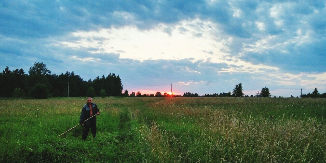 field, sky, one person, cloud - sky, nature, real people, grass, beauty in nature, outdoors, standing, growth, leisure activity, landscape, tranquil scene, scenics, tranquility, lifestyles, day, men, full length, tree, sunset, one man only, adult, people