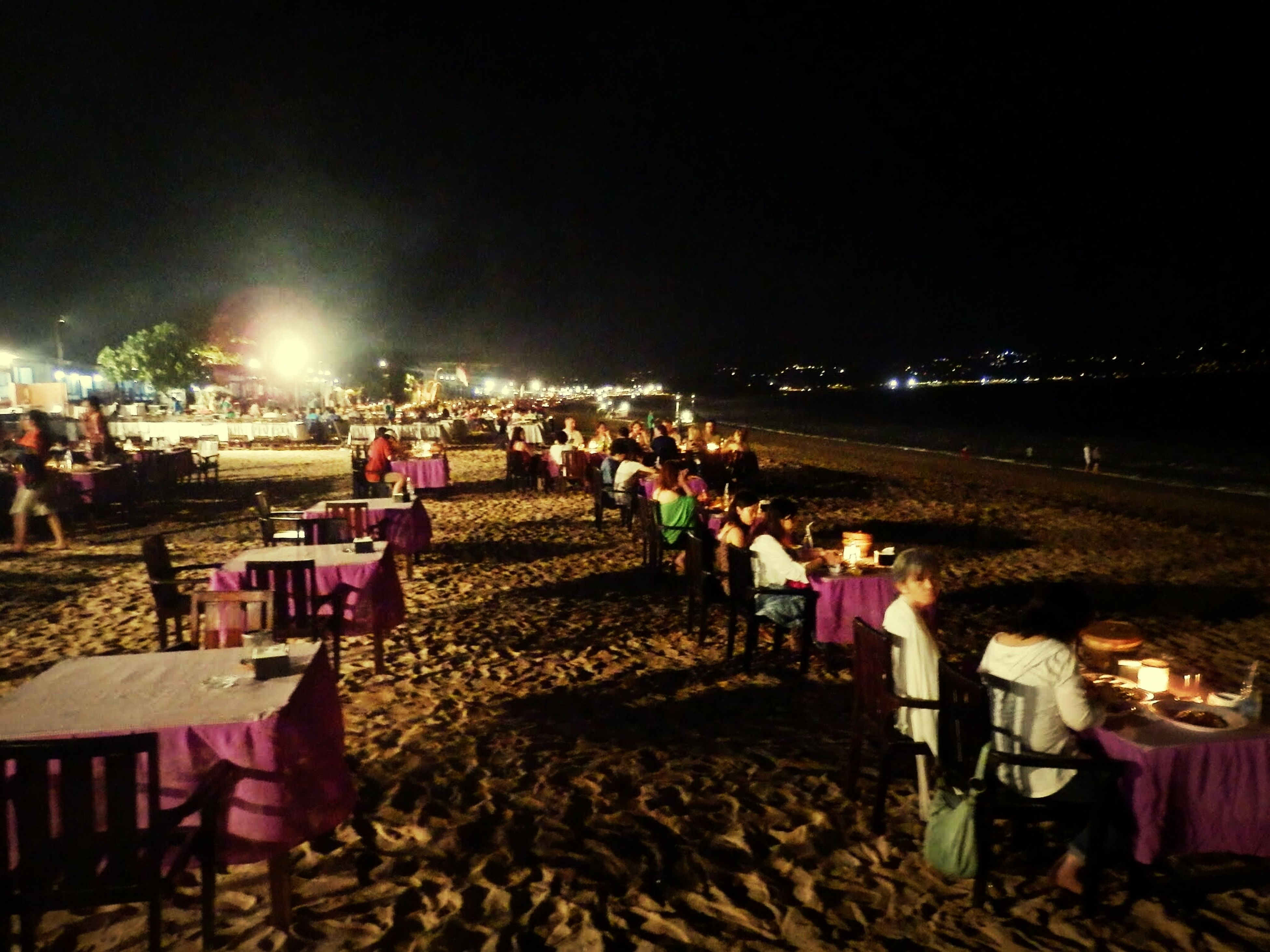 night, illuminated, large group of people, lifestyles, men, person, beach, leisure activity, sky, lighting equipment, outdoors, building exterior, mixed age range, abundance, walking, street, large group of objects, sand, built structure
