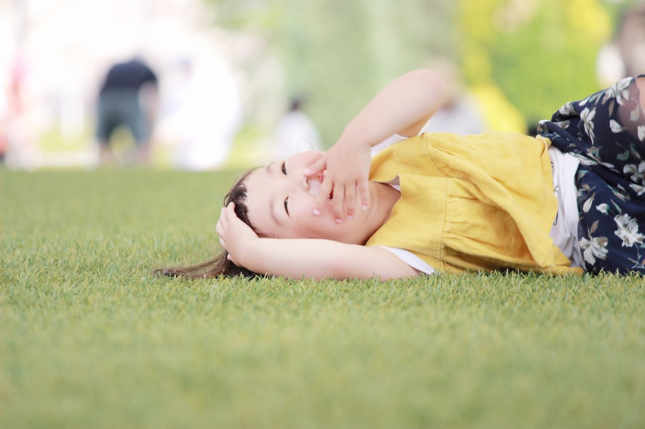 Happy Girl Covering Face While Lying On Grassy Field