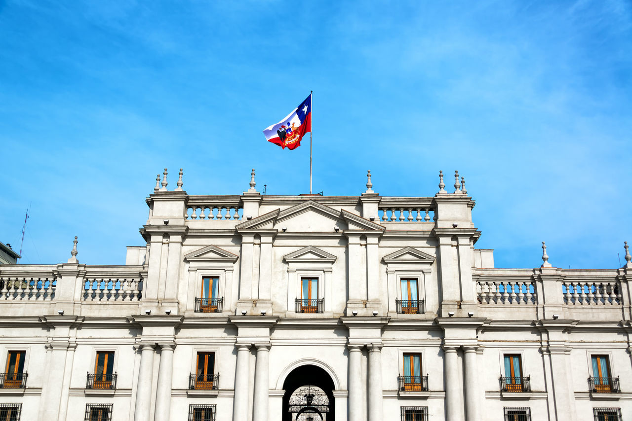 View of the facade of La Moneda Palace, the presidential palace in Santiago, Chile Architecture Blue Blue Sky Chile City Downtown Flag Historic Historical Building La Moneda La Moneda-Casa De Gobierno Latin America Palace Presidential Santiago Santiago De Chile Sky South America Tourism Travel Travel Destinations Urban