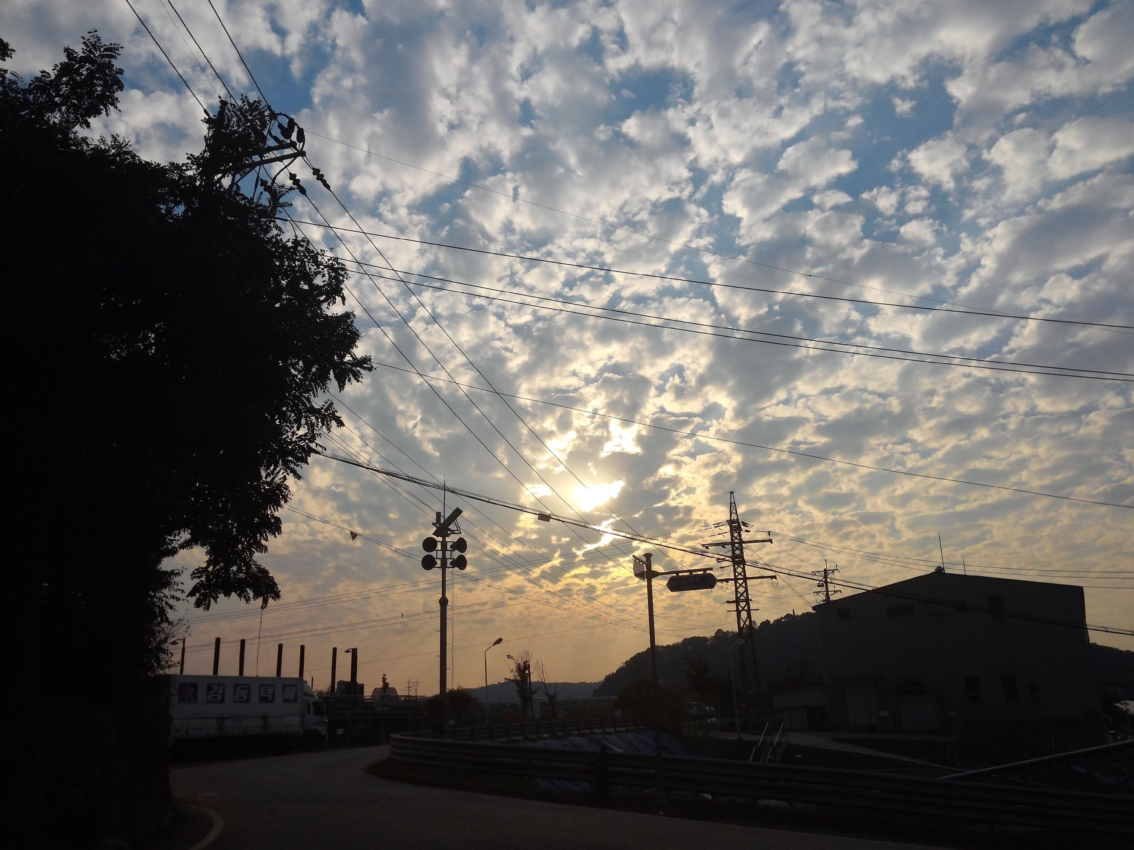 electricity pylon, sky, power line, silhouette, cloud - sky, sunset, electricity, power supply, fuel and power generation, cloudy, building exterior, tree, road, connection, street light, transportation, cloud, cable, street, built structure