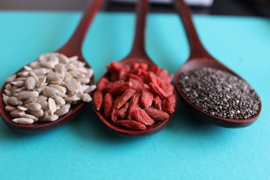 Healthy seeds on five wood spoons over blue background Chia Seed Close-up Dried Fruit Focus On Foreground Food Food And Drink Freshness Gojiberries Healthy Eating Indoors  Ingredient Large Group Of Objects No People Red Still Life Sunflower Seeds Table