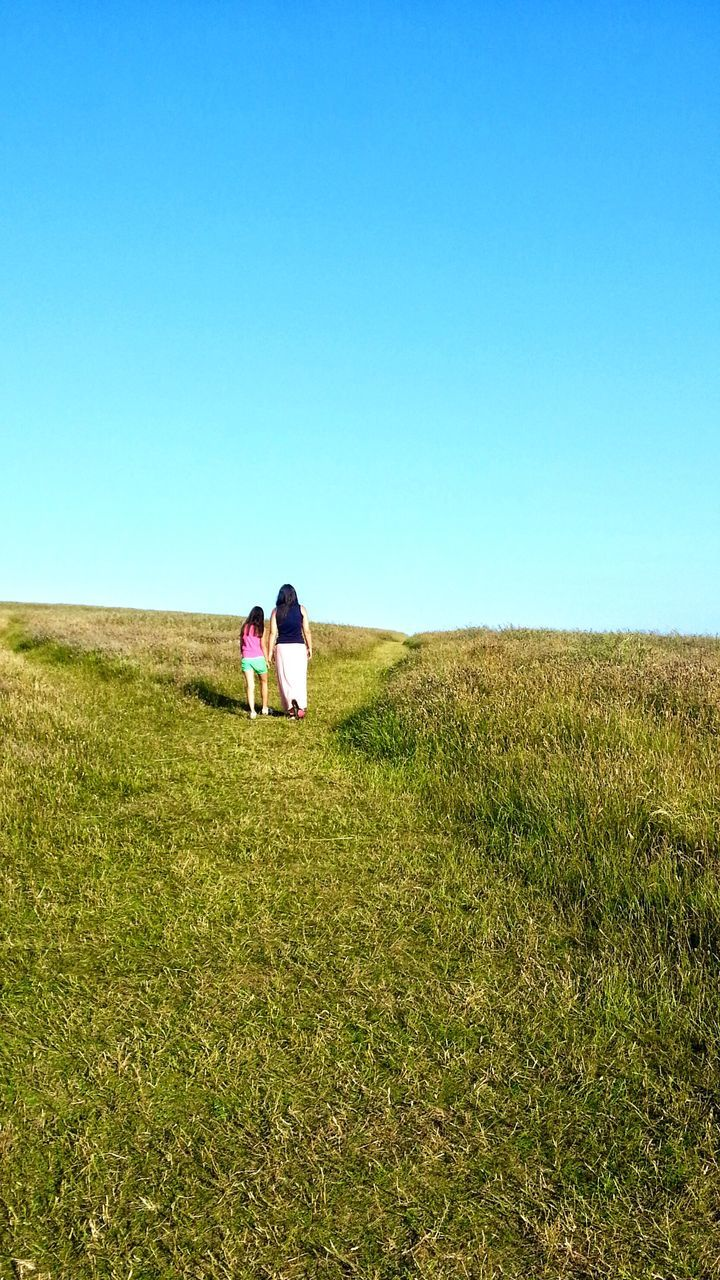 field, clear sky, copy space, two people, nature, grass, rear view, togetherness, real people, outdoors, day, walking, lifestyles, men, landscape, women, standing, leisure activity, blue, young women, full length, scenics, bonding, beauty in nature, growth, young adult, sky, people