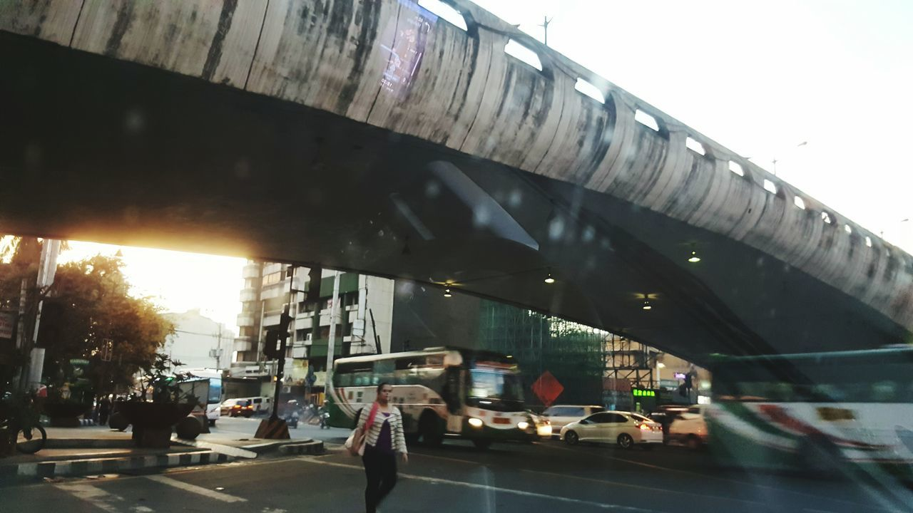 car, transportation, bridge - man made structure, architecture, land vehicle, connection, built structure, road, street, mode of transport, traffic, city, highway, city life, outdoors, bridge, day, building exterior, real people, under, sky