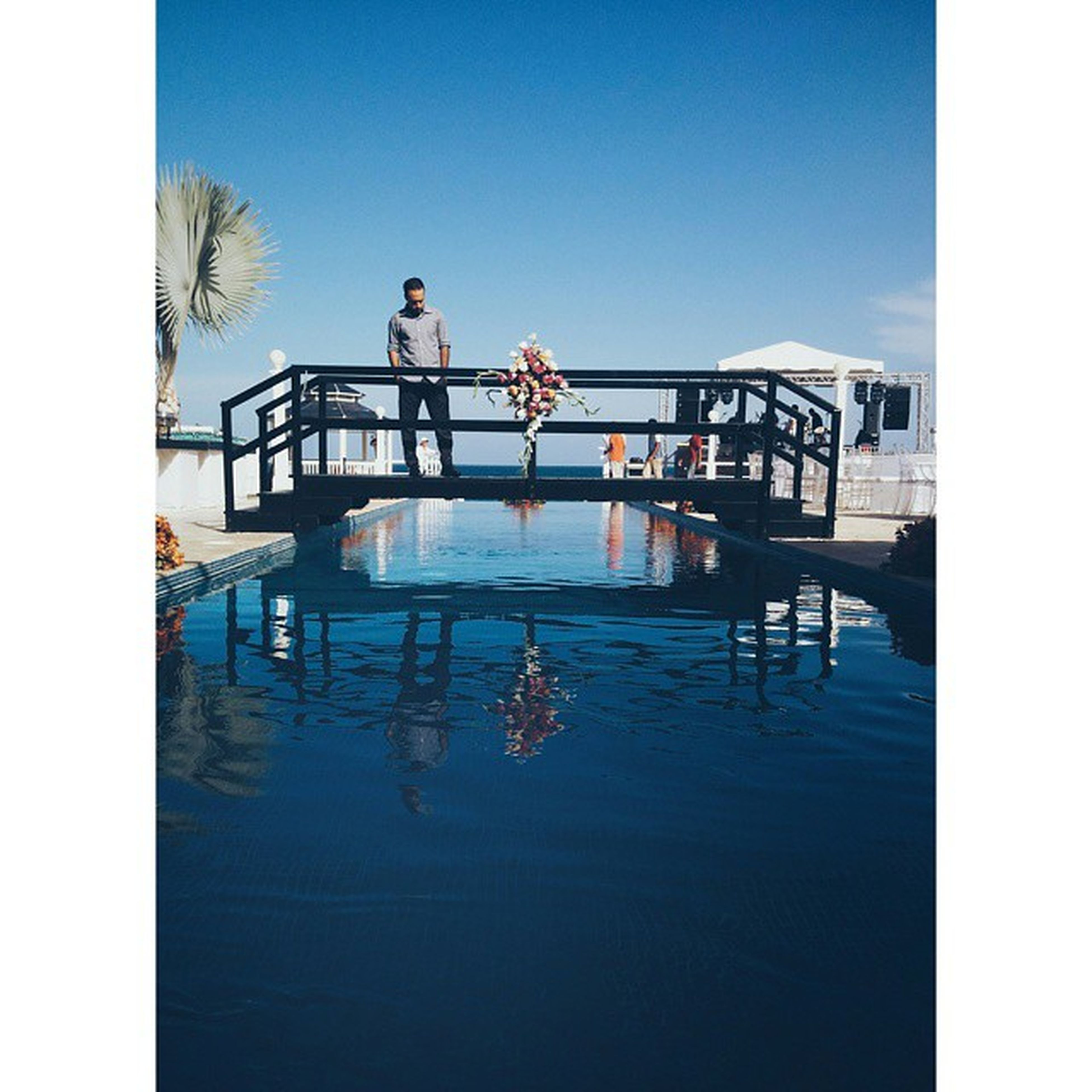 transfer print, water, clear sky, blue, swimming pool, auto post production filter, reflection, built structure, architecture, lifestyles, leisure activity, copy space, waterfront, men, day, railing, building exterior, sunlight