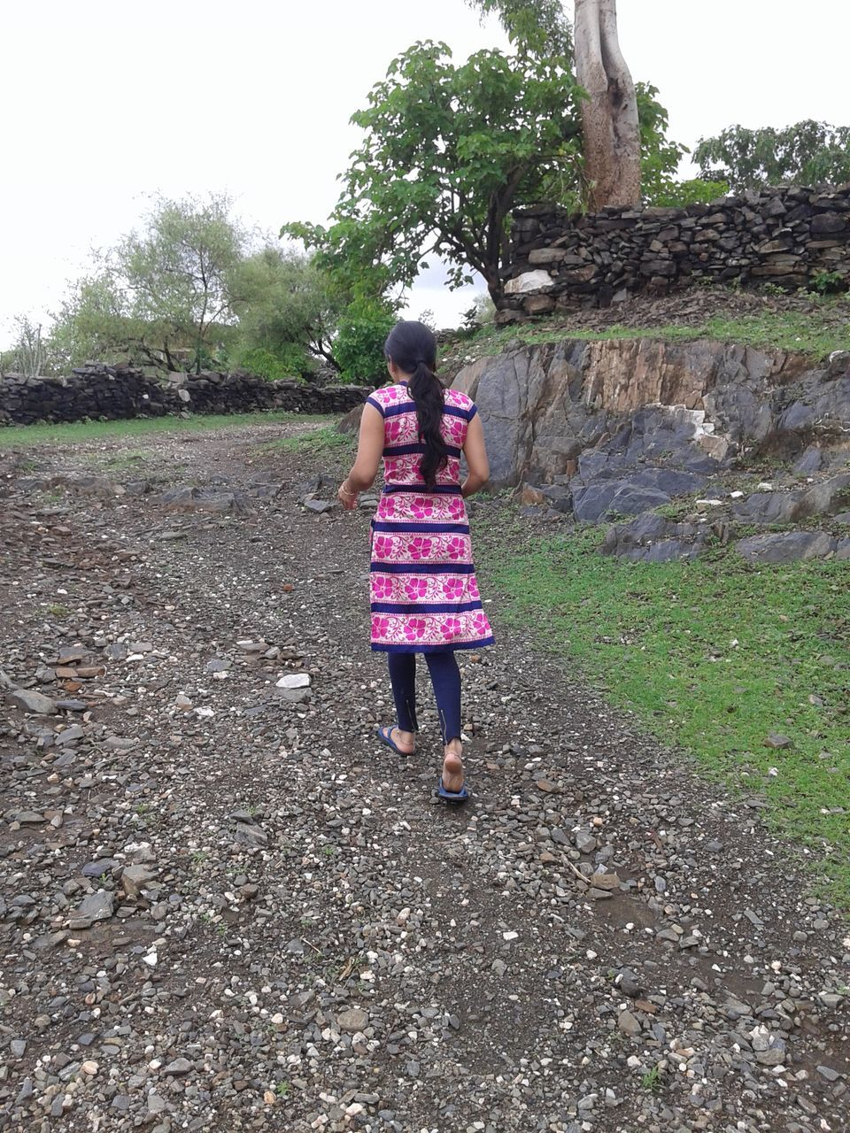 Rear View Of Woman Walking On Dirt Road