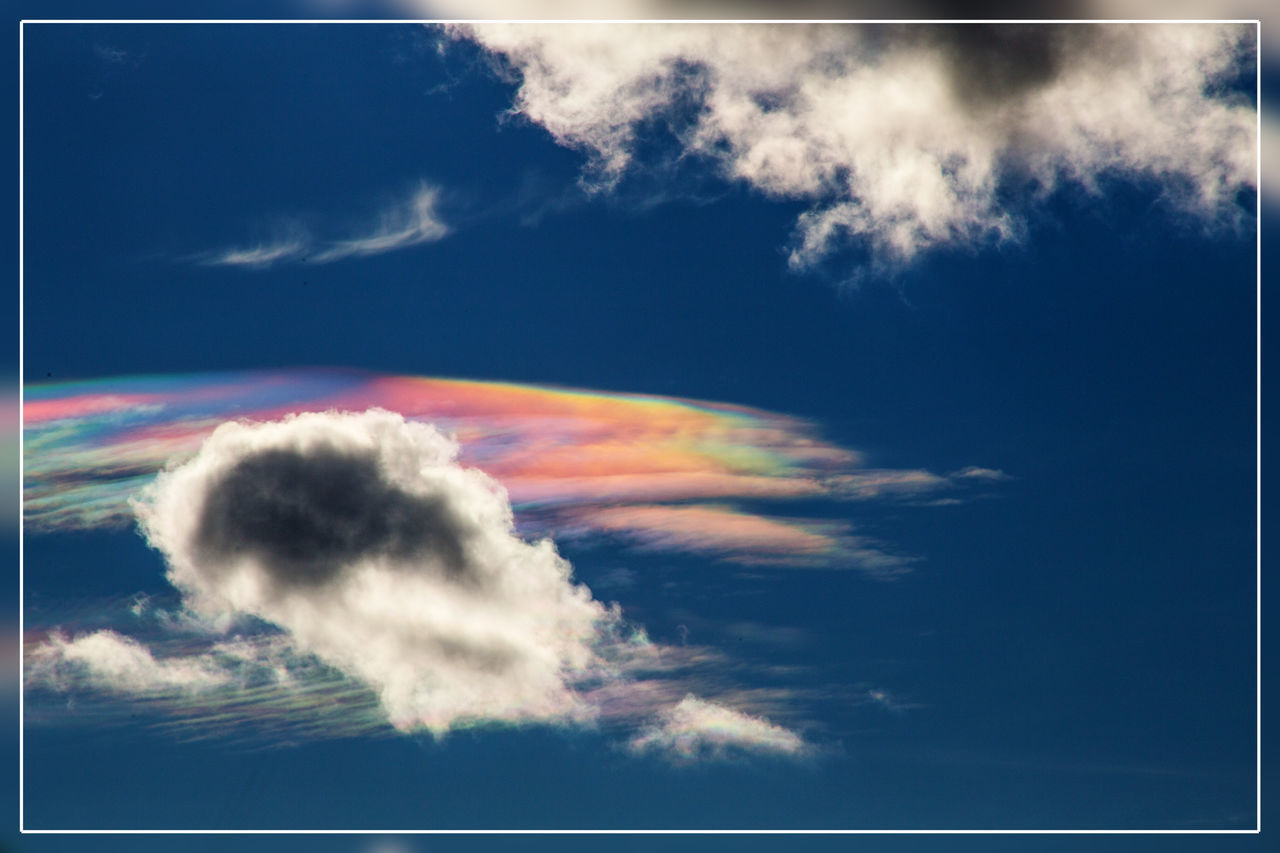 """Halo appearance due to refraction of sunlight in very high ice-clounds (cirrus clouds, about 8-11km) Only the rainbow colored cloud is that high. The """"normal"""" ones are usual low cumulus clouds at about 1km. Cirrus Cloud - Sky Day Flying Halo No People Outdoors Rainbow Rainbow Colors Sky Vapor Trail Weather Weather Photography"""