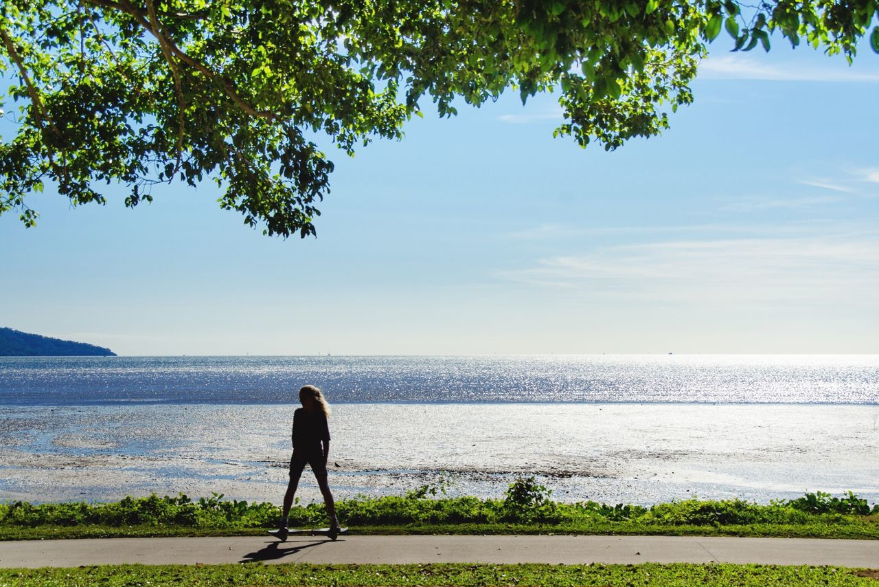 sea, nature, water, tree, beauty in nature, scenics, one person, real people, standing, beach, tranquility, full length, tranquil scene, outdoors, leisure activity, day, horizon over water, men, sky, people
