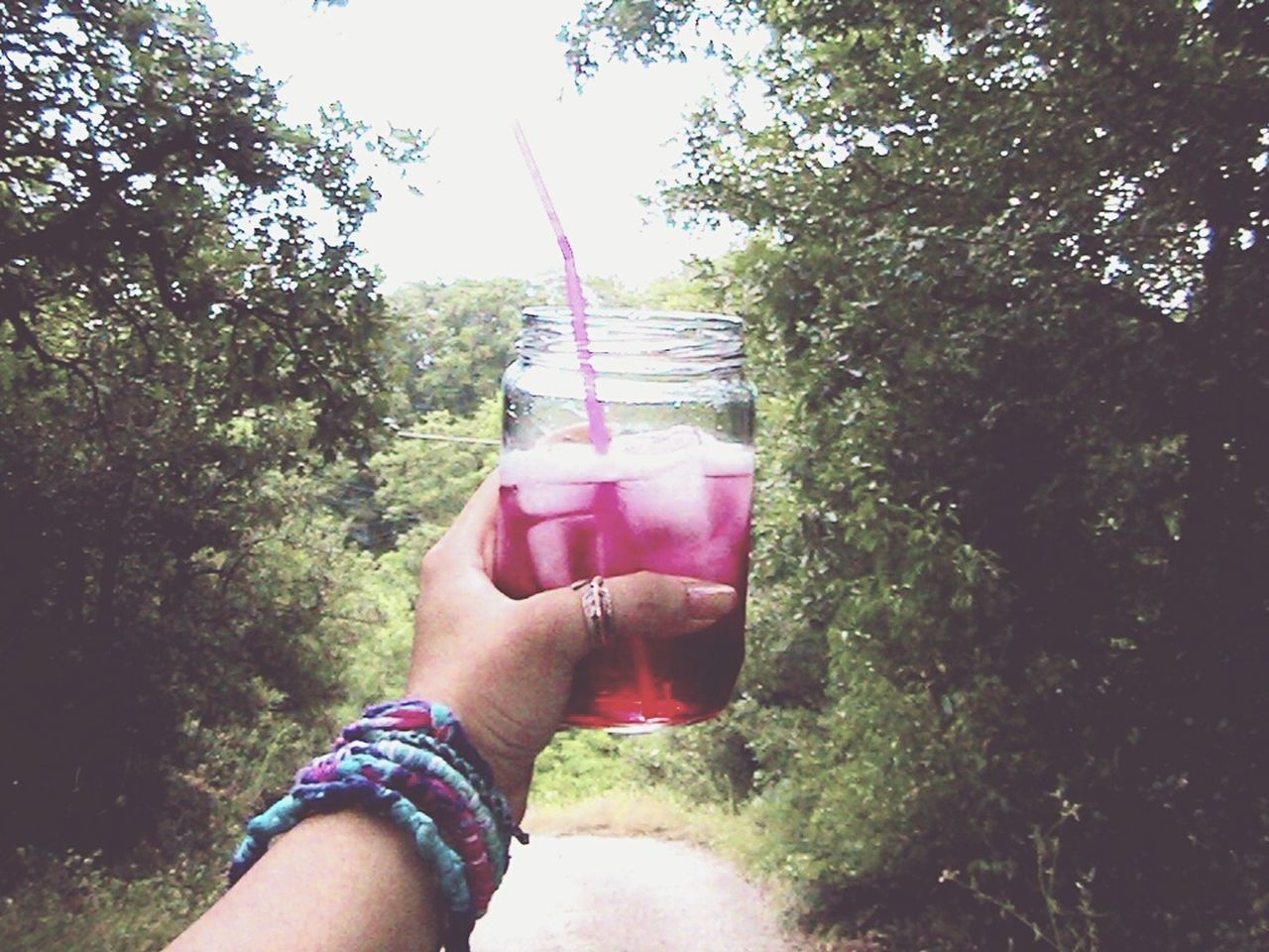 human hand, holding, one person, real people, human body part, personal perspective, refreshment, drink, tree, food and drink, drinking straw, day, outdoors, freshness, lifestyles, nature, close-up, sky, water, beauty in nature, people