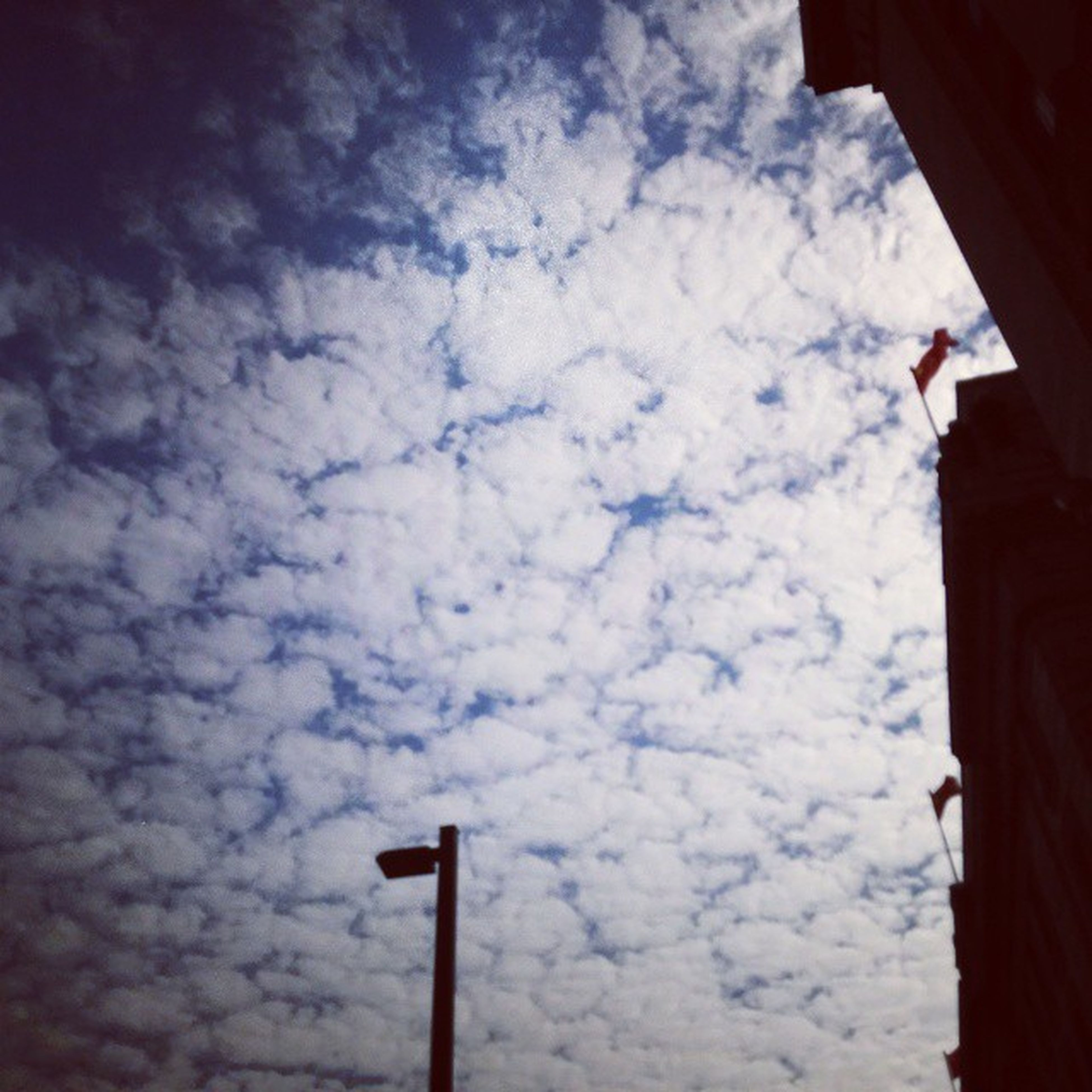low angle view, sky, cloud - sky, built structure, building exterior, architecture, cloud, cloudy, flag, weather, outdoors, day, no people, silhouette, pole, high section, street light, nature, building, religion