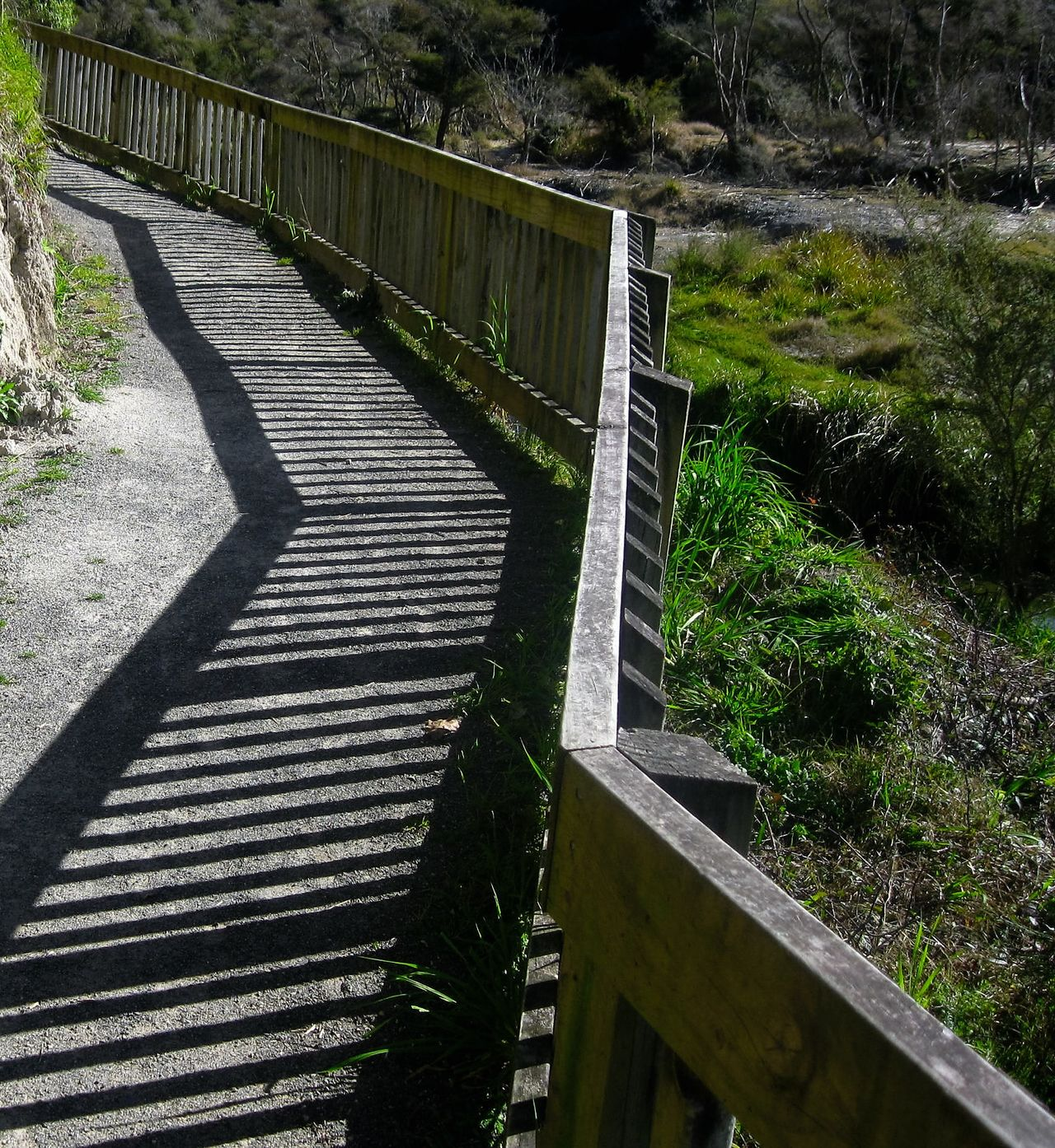 Striped shadows cast by the wooden fence laying a pattern on the walkway by the hillside Hill Light And Shadows Paris Shadows Striped Pattern The Way Forward Tranquility Tree Walkway Wooden Fence Wooden Railing
