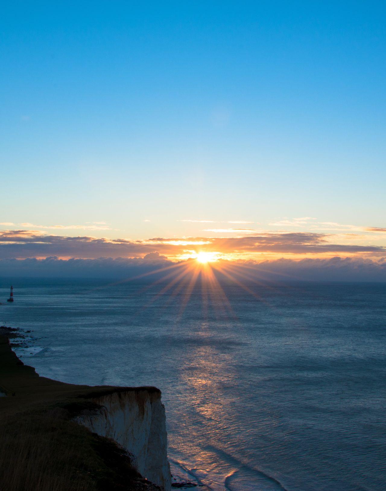 Sunburst. Dawn Of A New Day Sunrise Beachy Head Lighthouse Cliff Sea And Sky Landscape_Collection Blue Sky