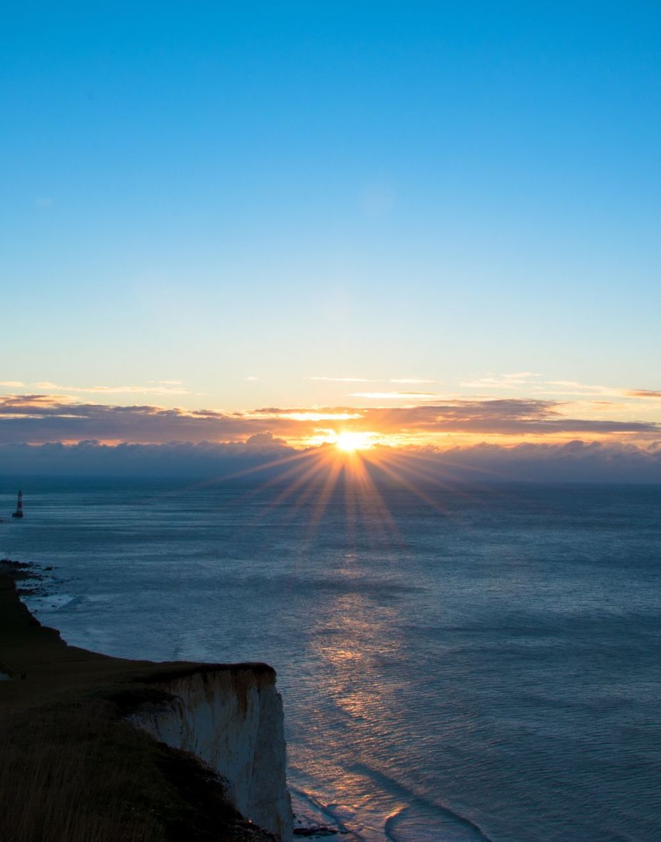 Sunburst. Dawn Of A New Day Sunrise Beachy Head Lighthouse Cliff Sea And Sky Landscape_Collection Blue Sky