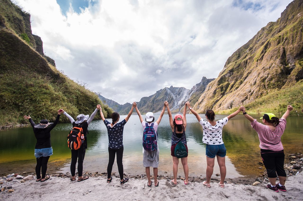 mountain, real people, sky, cloud - sky, men, mountain range, casual clothing, arms raised, rear view, standing, day, togetherness, nature, women, leisure activity, outdoors, landscape, lifestyles, scenics, young men, beauty in nature, friendship, full length, young women, panoramic, young adult, adult, people
