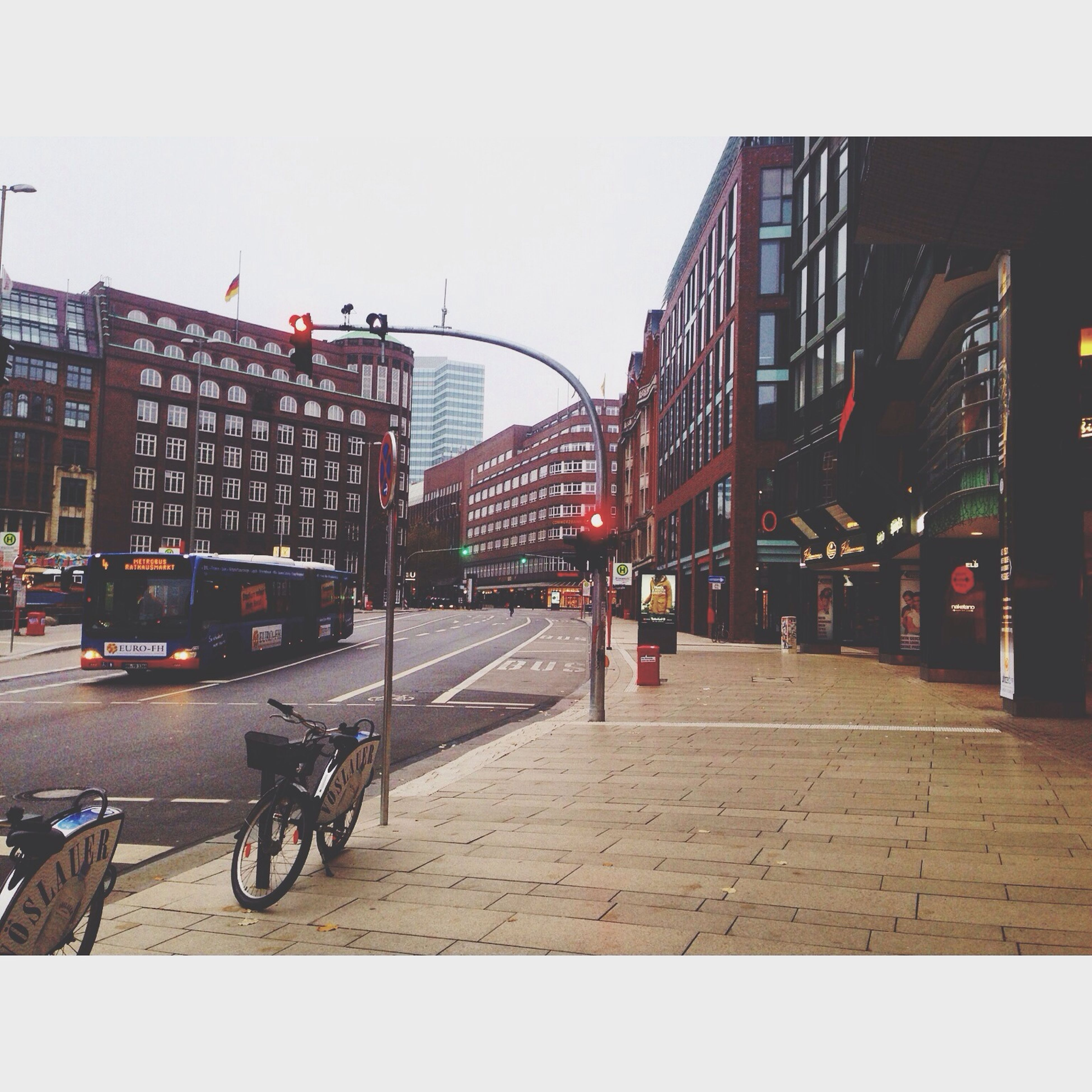 building exterior, architecture, built structure, transportation, city, mode of transport, clear sky, street, land vehicle, street light, bicycle, car, city life, the way forward, city street, building, incidental people, sky, road, diminishing perspective