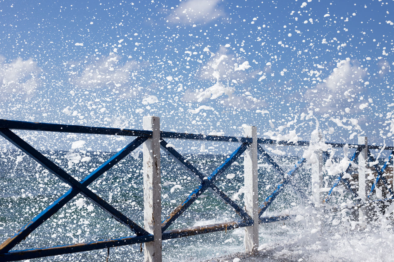 During flood some big waves broke onto rocks and created massive foam next to the handrail. It looks like snow falling down from the sky. Atlantic Ocean Discover Nature Falling Down Foam Handrail  Nature Outdoors Power Of The Sea Salt Water Sea Spray Summer Travel White And Blue Wood - Material Motion Freeze Split Second Dynamic Force Energy