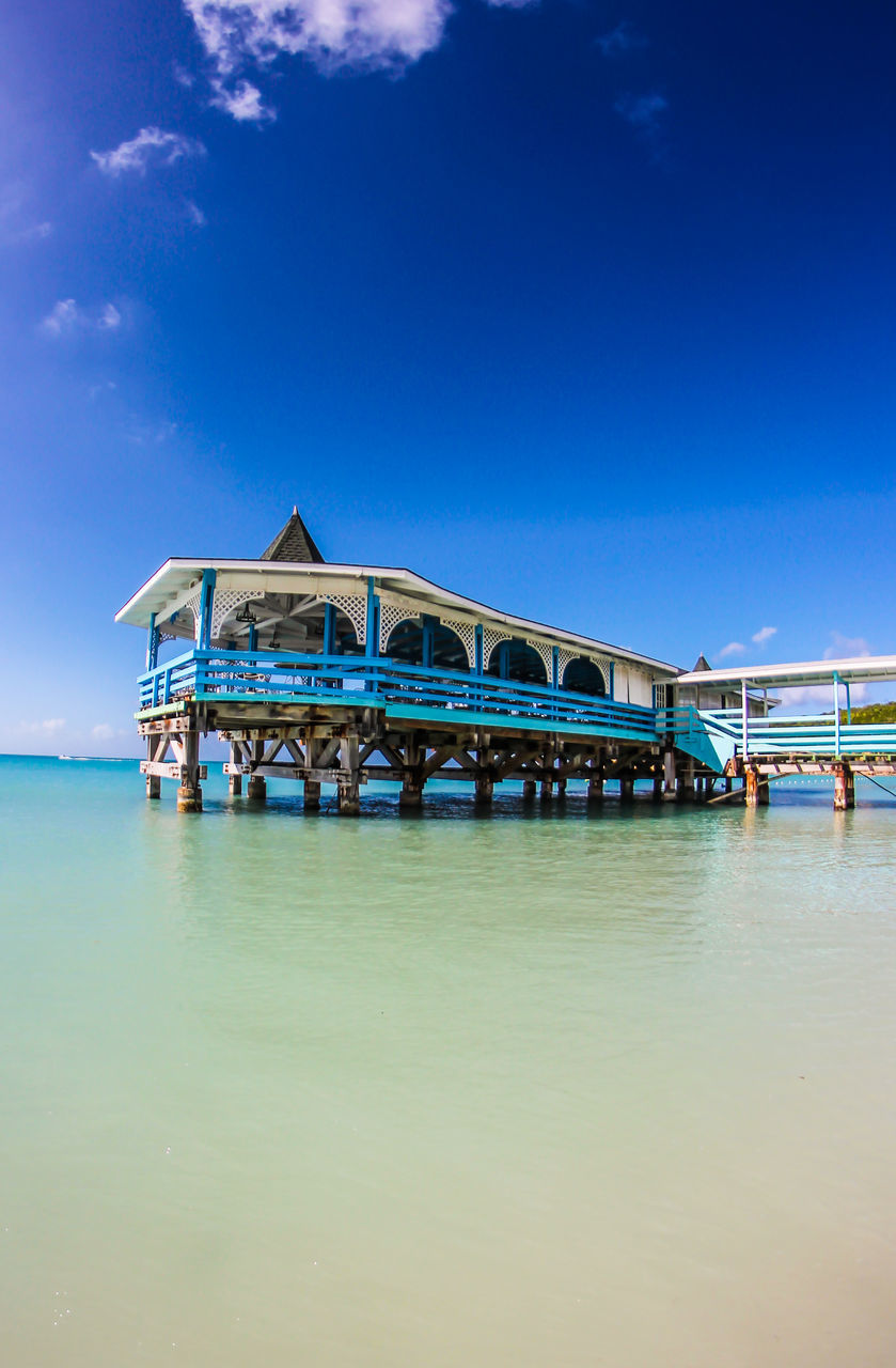 water, built structure, architecture, sky, sea, waterfront, day, vacations, blue, outdoors, nature, stilt house, beauty in nature, tranquility, tranquil scene, travel destinations, building exterior, no people, scenics, beach
