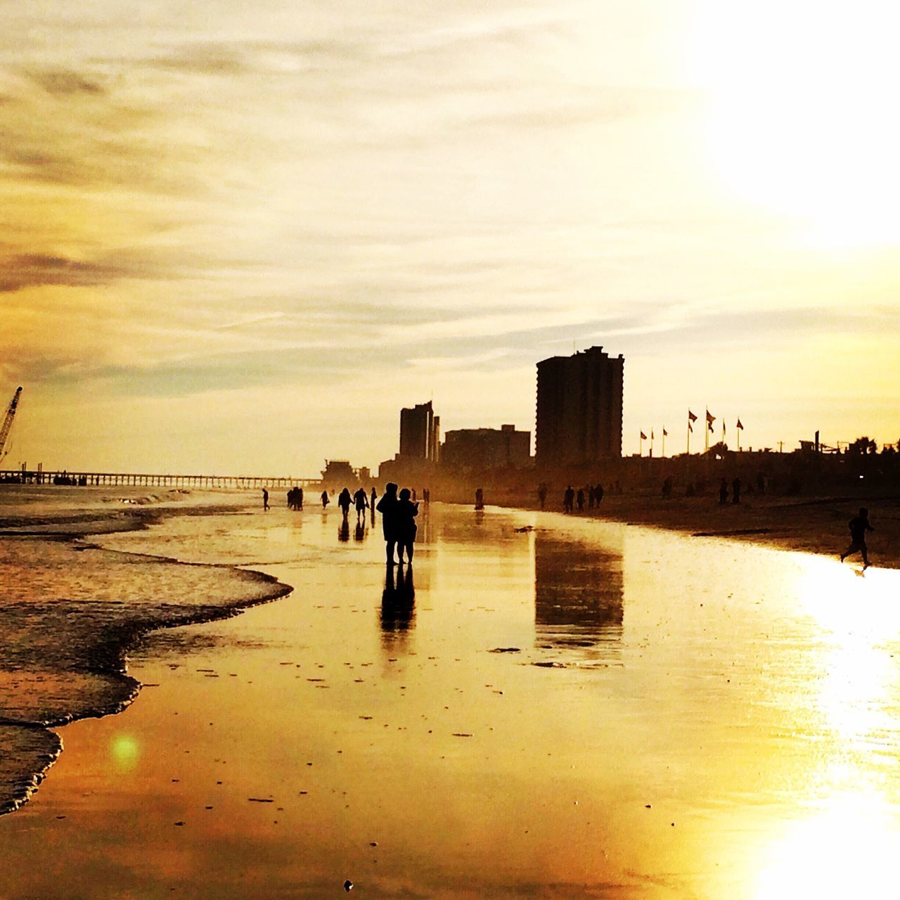 water, sky, architecture, beach, built structure, sea, sunset, reflection, nature, building exterior, outdoors, real people, men, beauty in nature, day, people