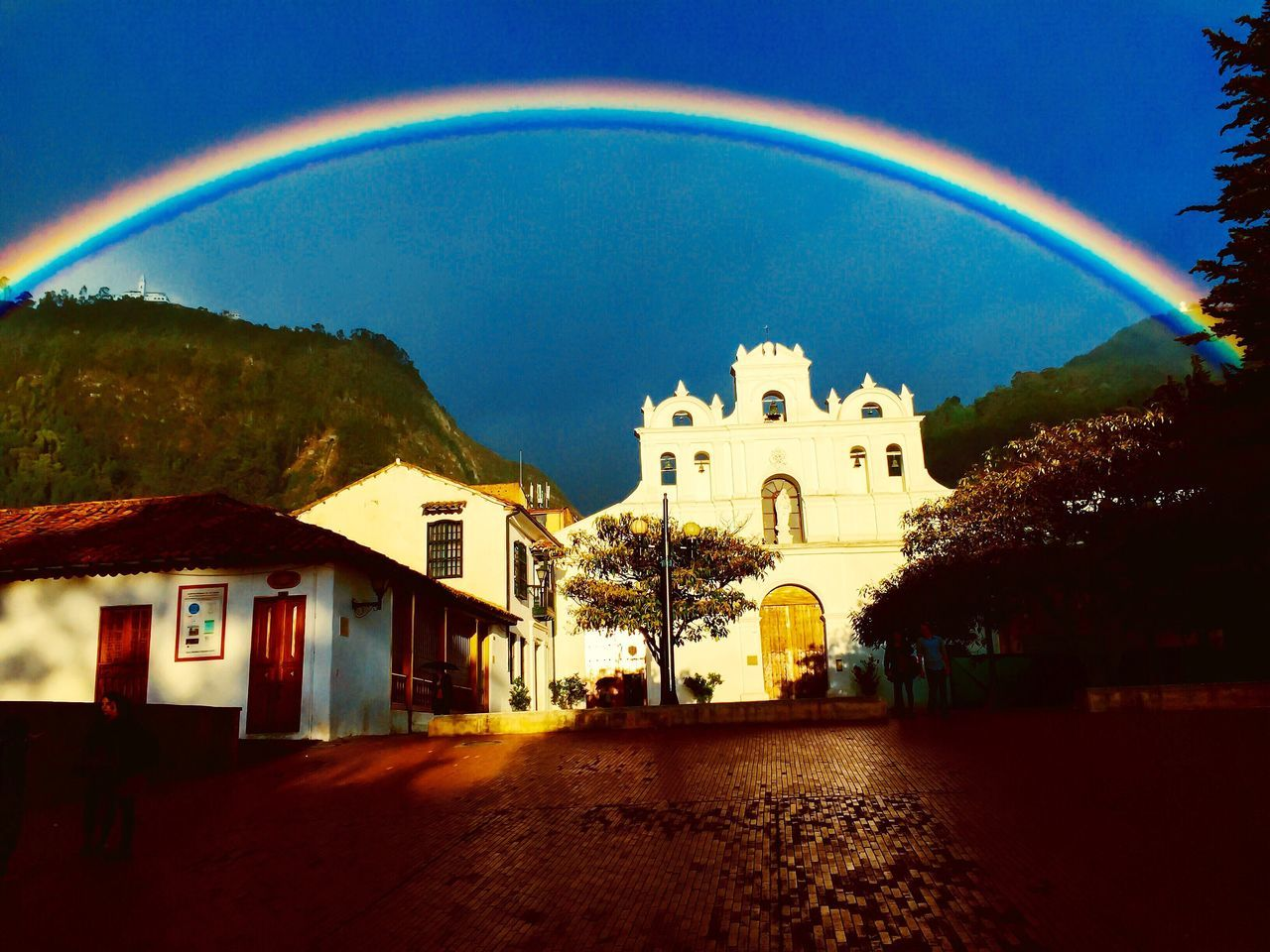 architecture, built structure, building exterior, arch, rainbow, sky, mountain, no people, spirituality, outdoors, day, nature, tree